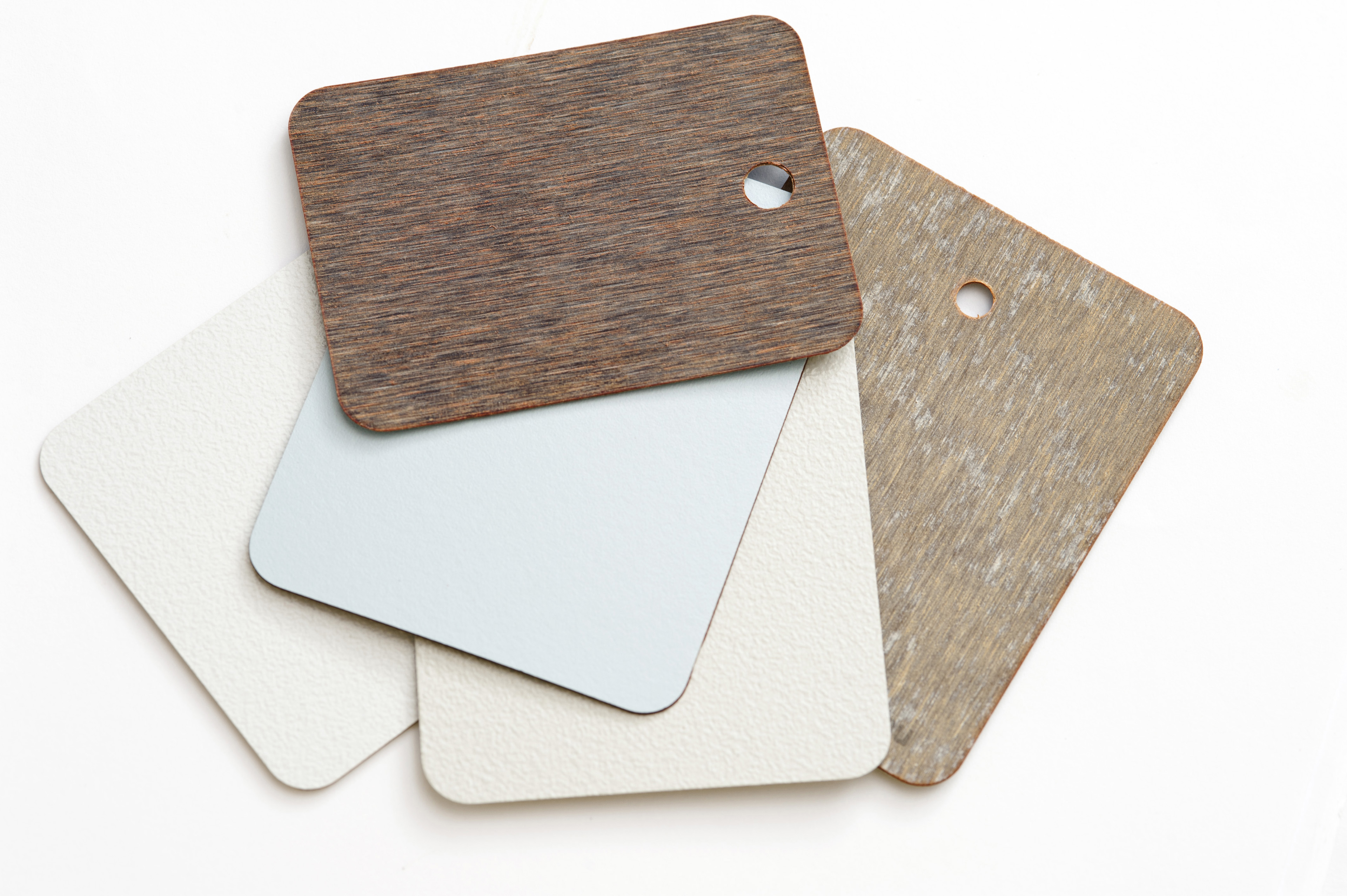 Pile of different neutral colored laminate swatches for interior coverings and surfaces in a house lying on top of each other on a white background