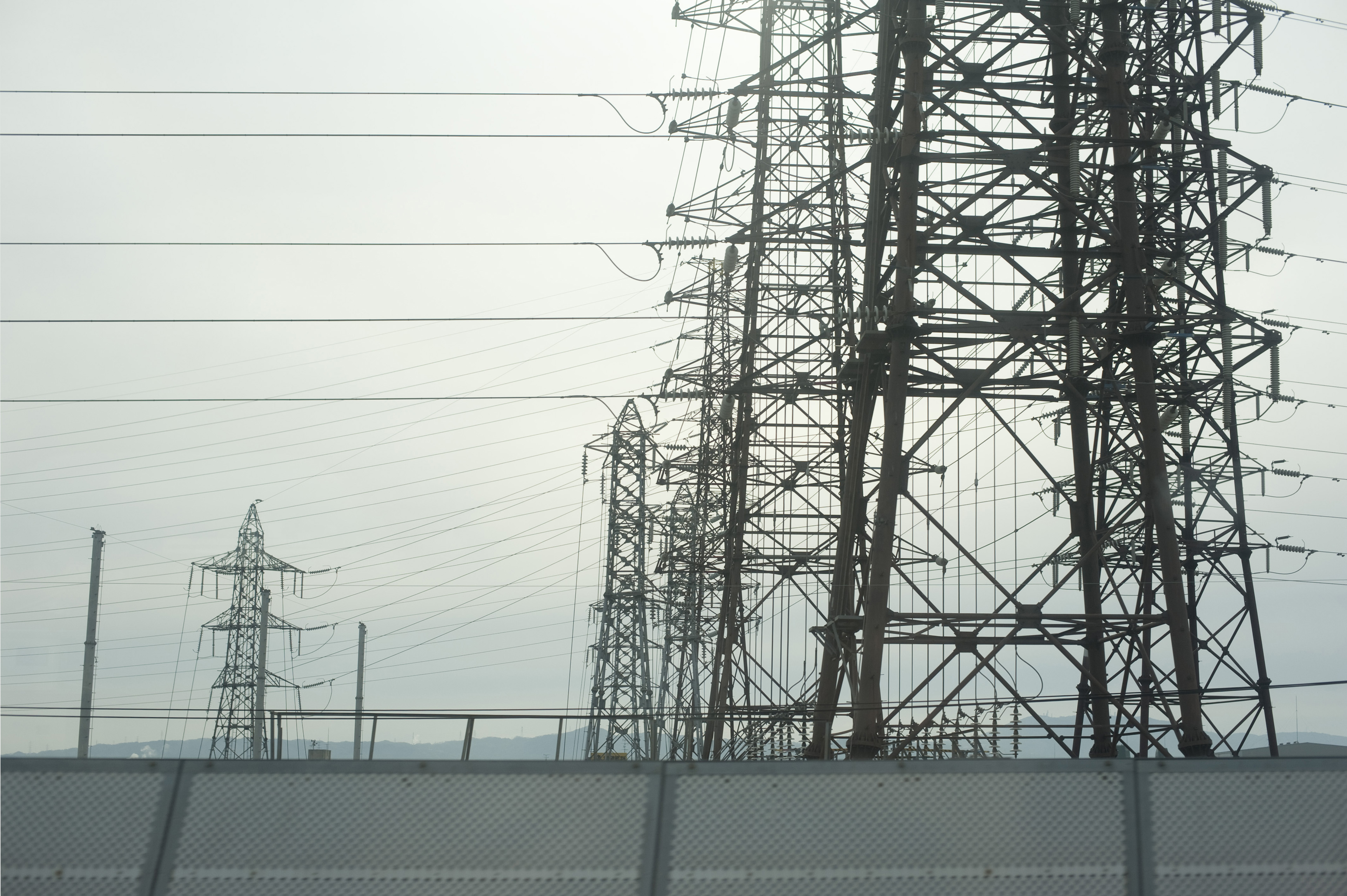 Group of large steel lattice power pylons supplying industry with electricity viewed on a grey misty day