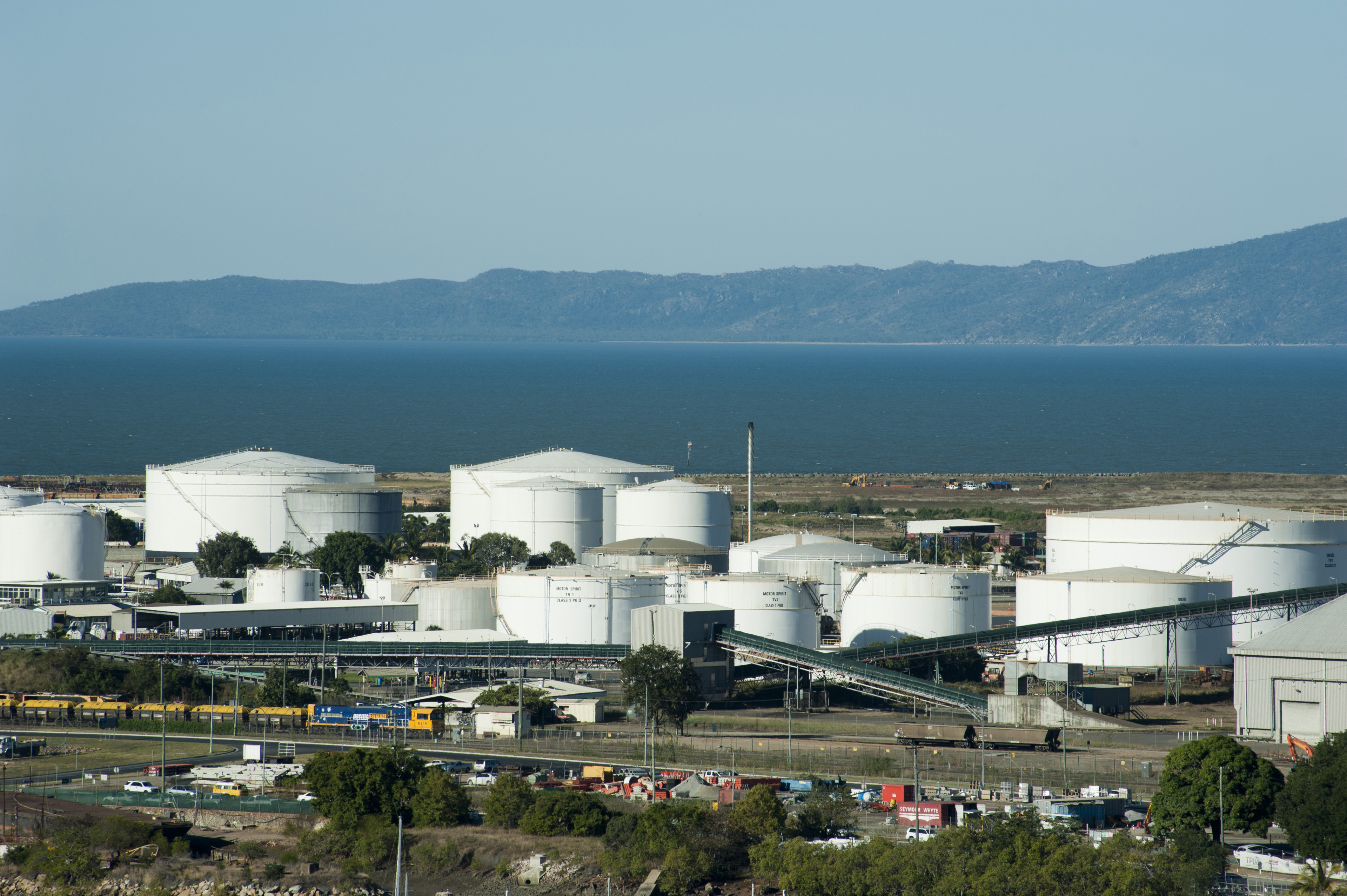 Large cylindrical storage tanks at a coastal industrial refinery for processing raw materials and resources