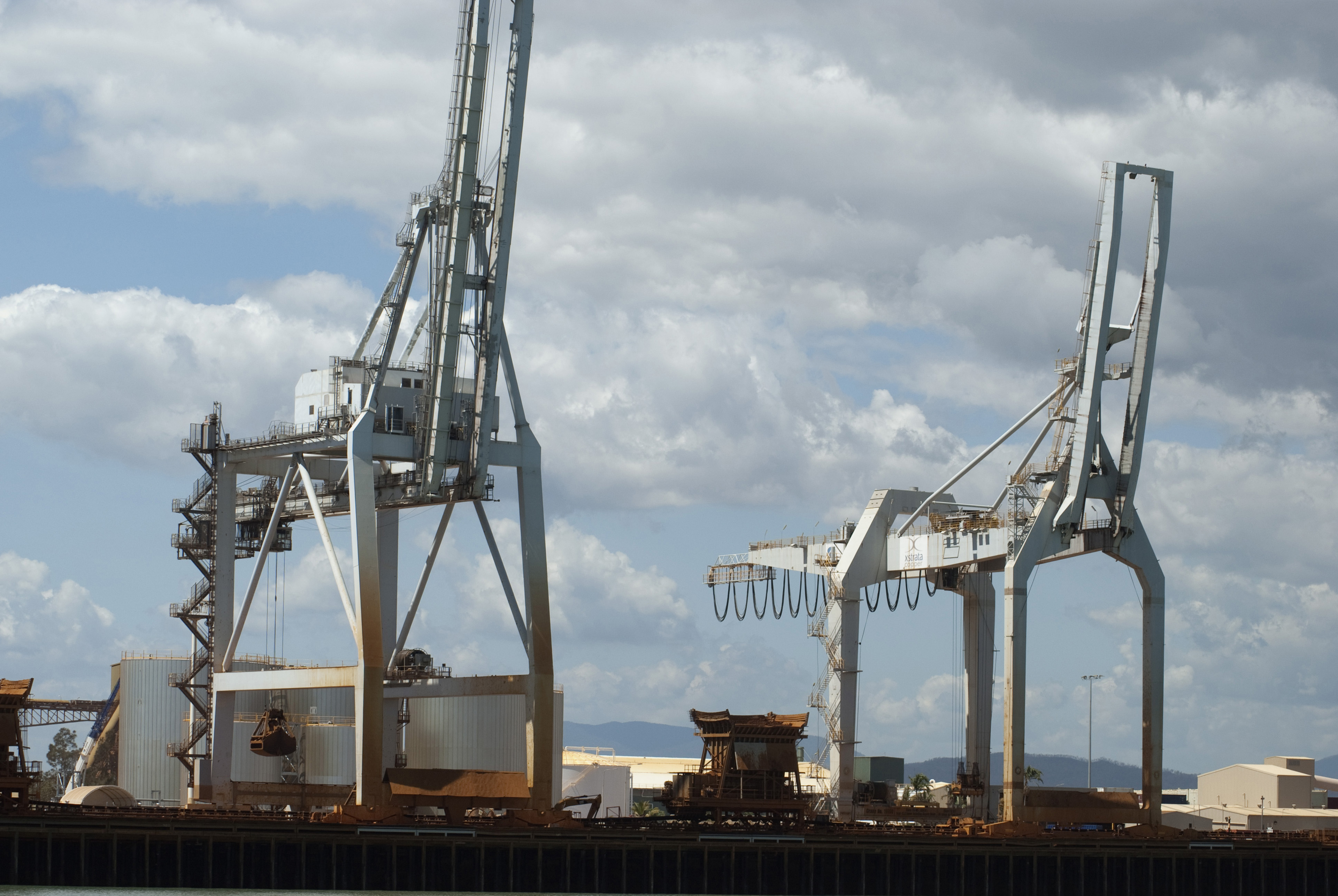 Detail of Loading Cranes at Coastal Shipping Terminal with Cloudy Blue Sky