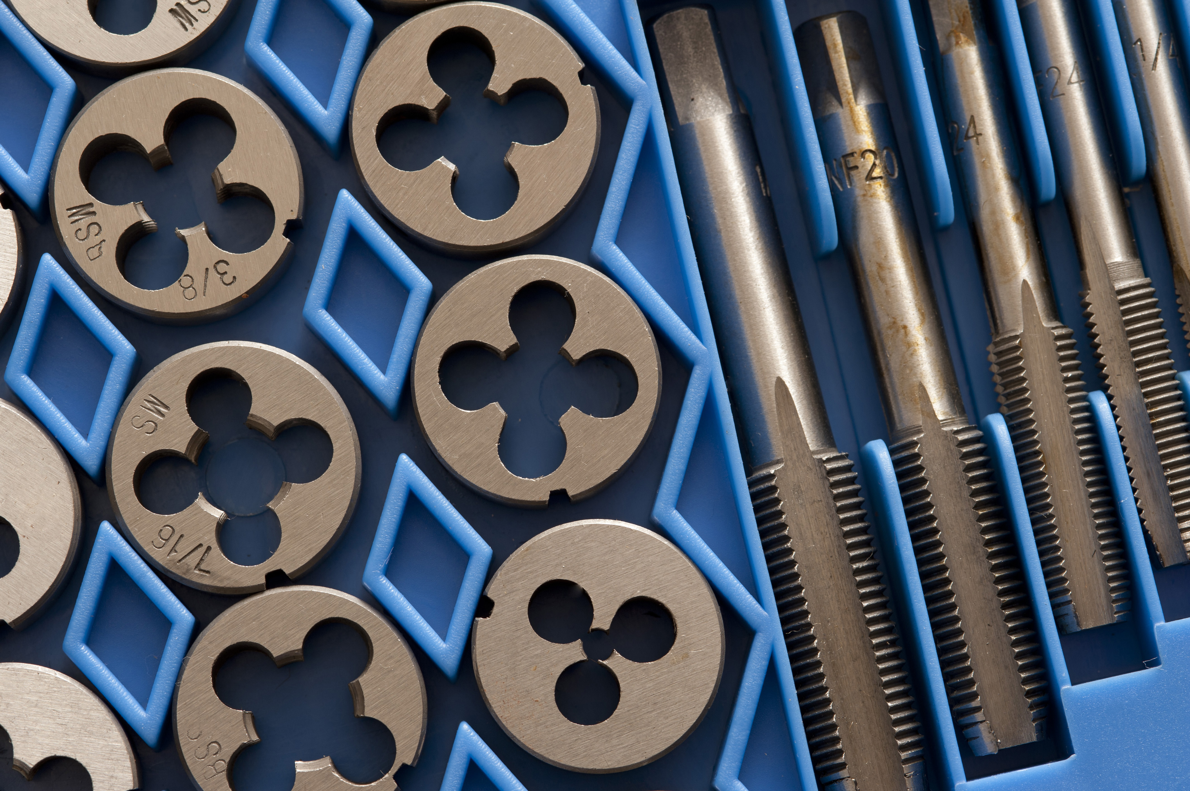 Set of taps and dies for producing screw threads, known as tapping and threading, in blue packaging, closeup view from above