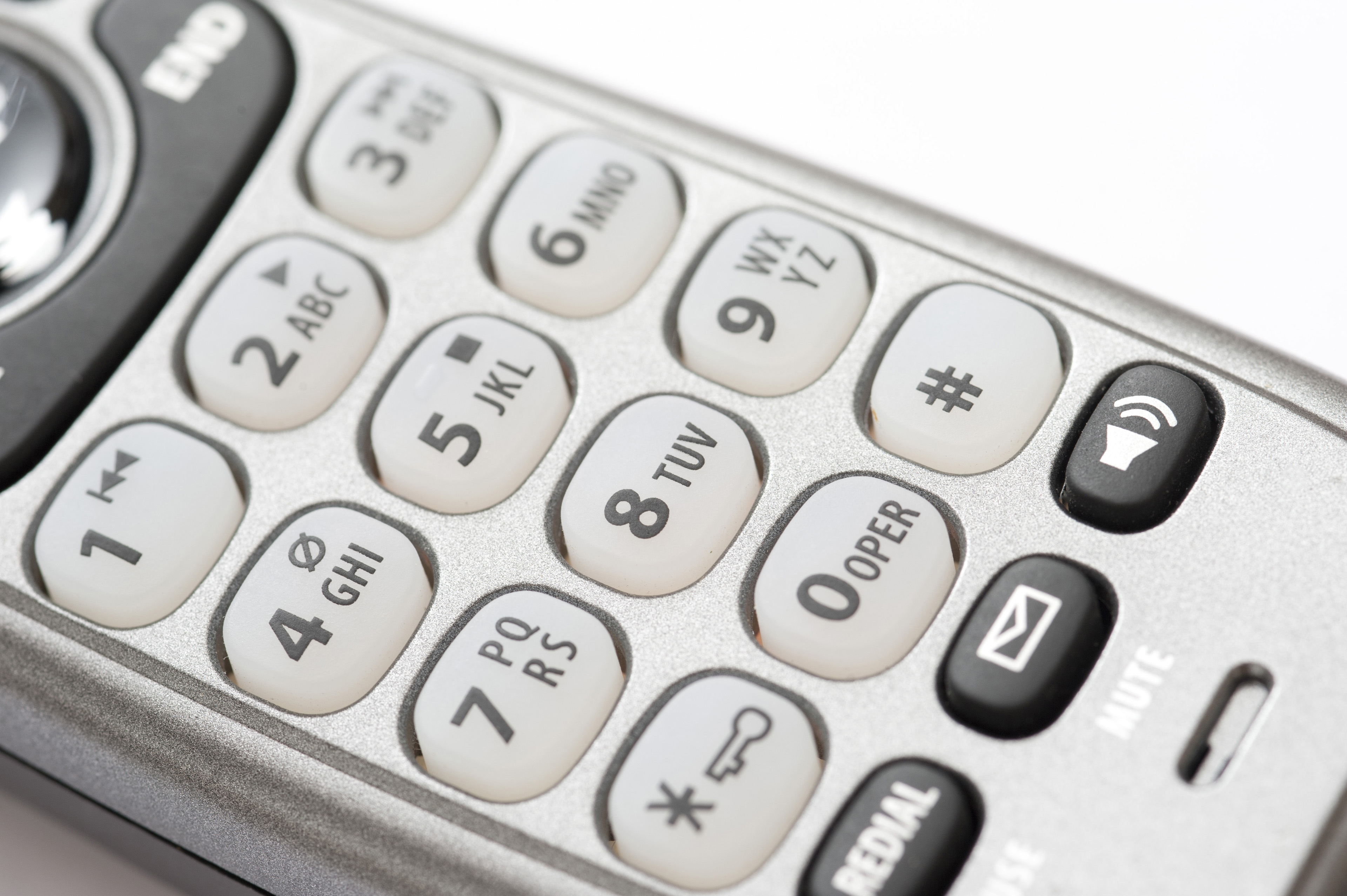 Close up of the alphanumeric keypad and function buttons on a telephone handset in a communications concept