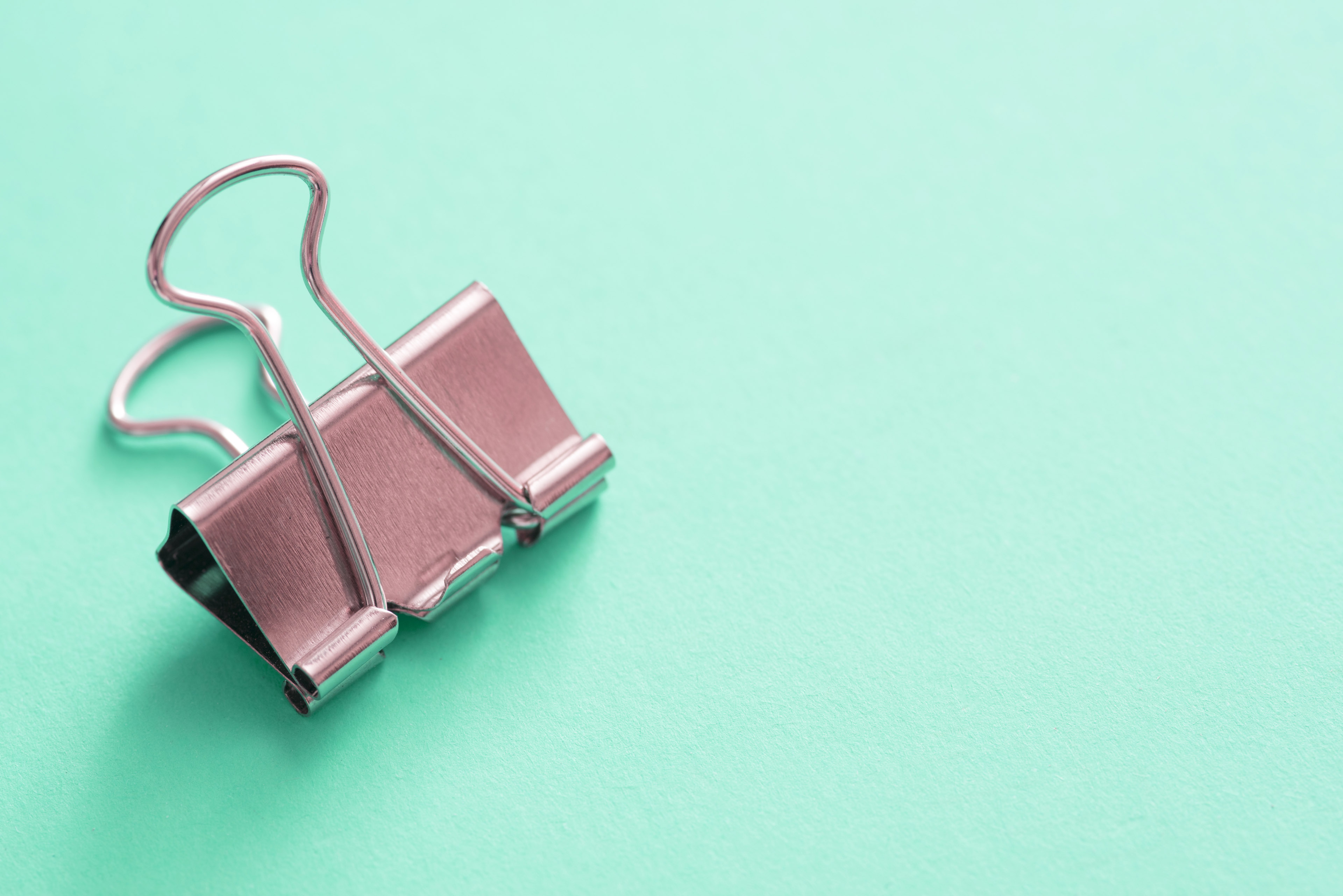 Single metal bulldog clip against mint background