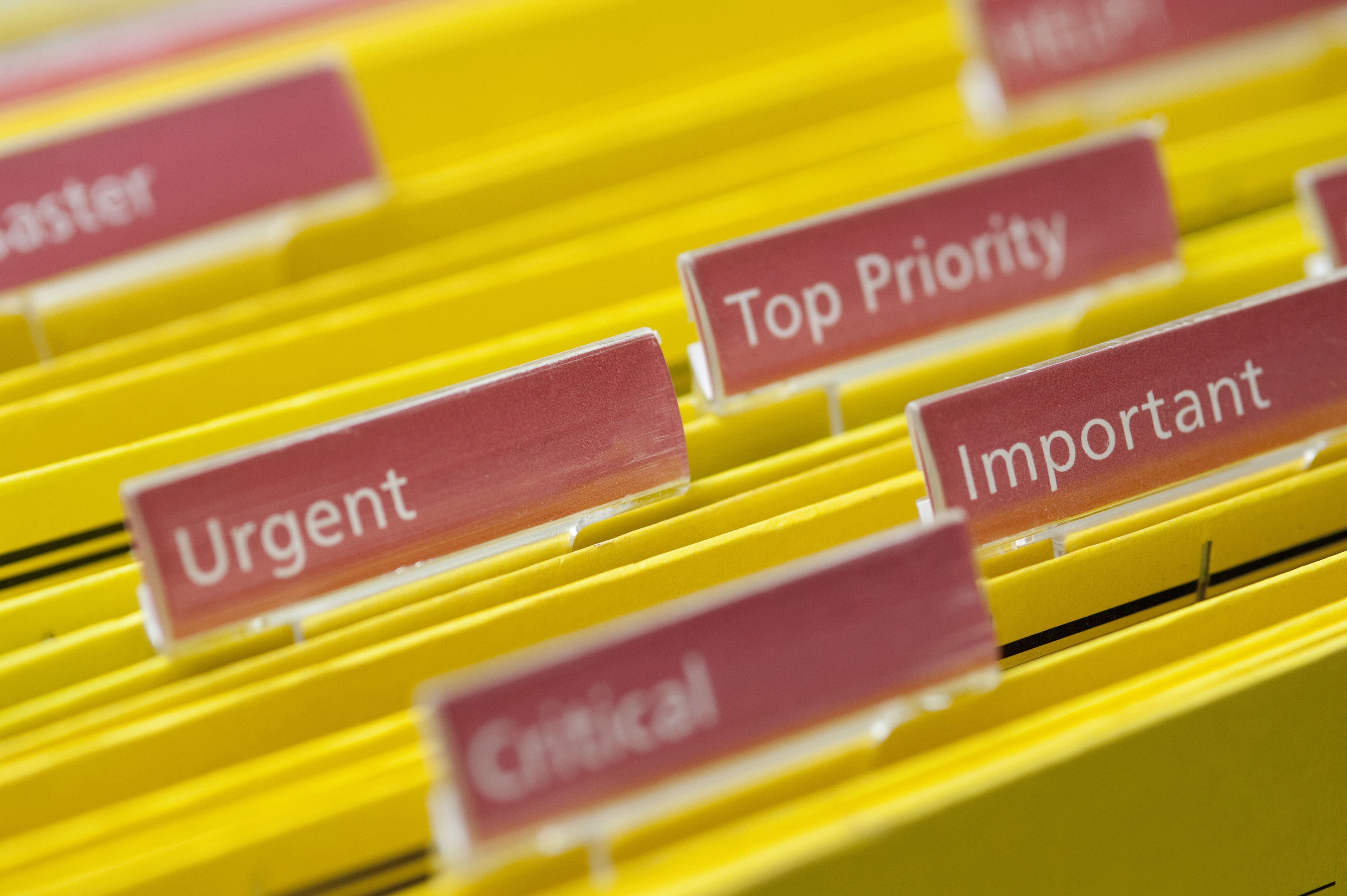Busy Concept - Close up Yellow Folders with Labels Emphasizing Urgent, Critical, Important and Top Priority Keywords.
