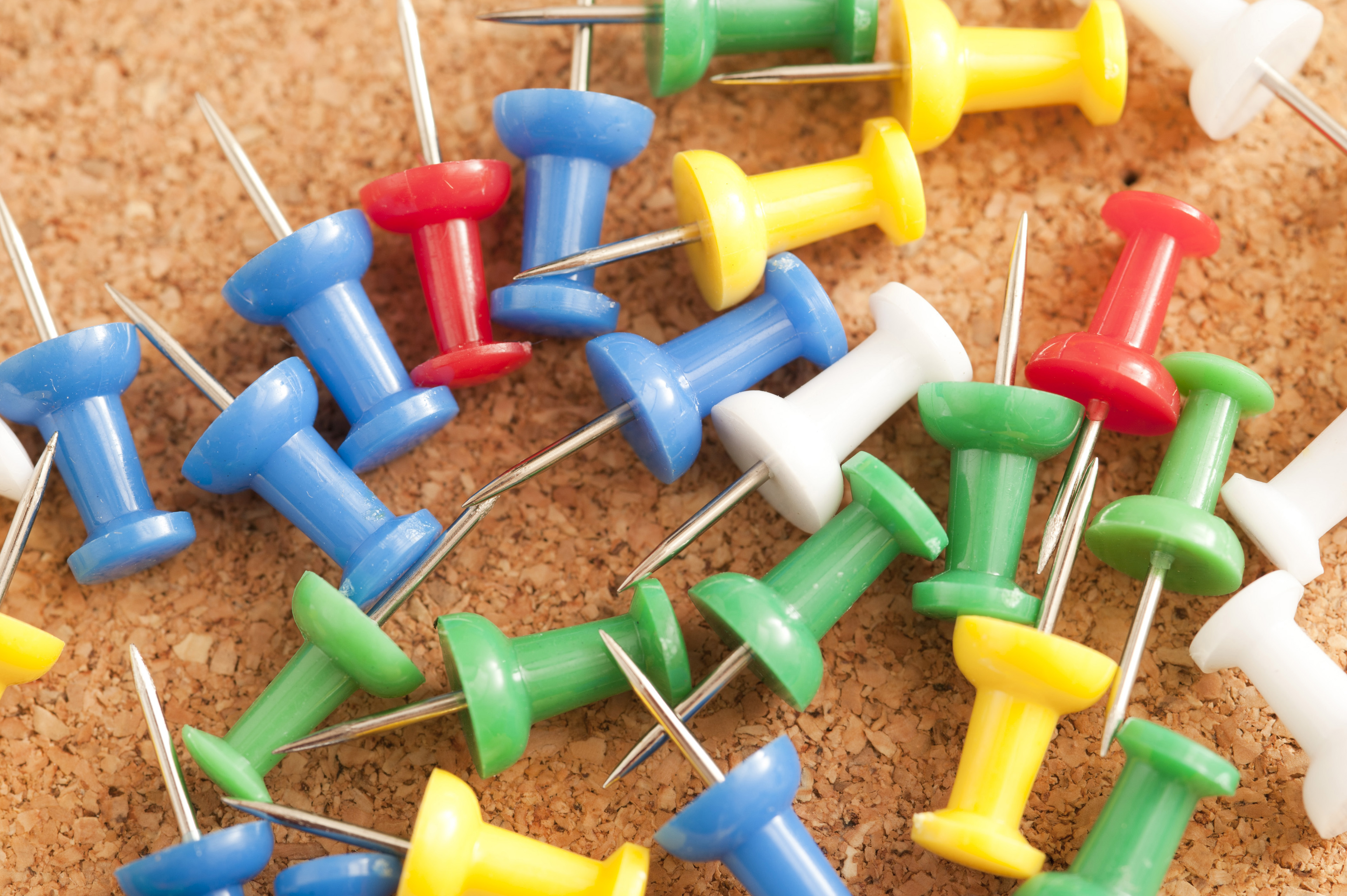 Close up Colorful Sharp Marker Pins on Top of Brown Cork Board