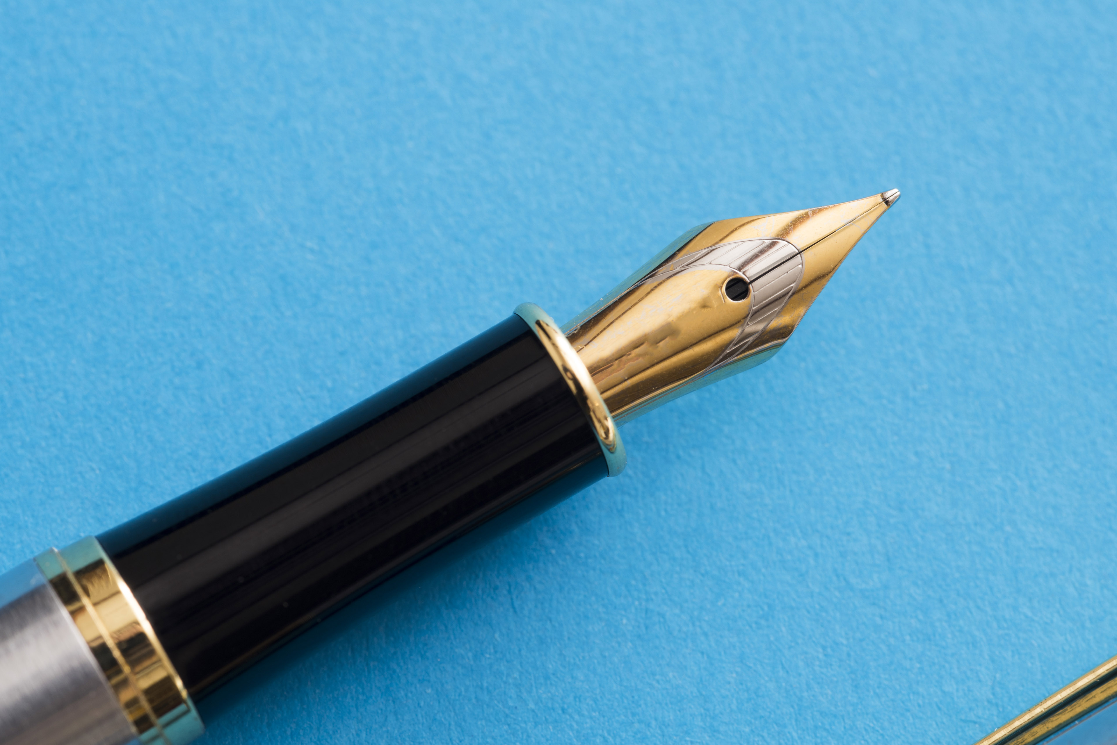 Close up of a calligraphy fountain pen tip isolated on a blue background with copy space.