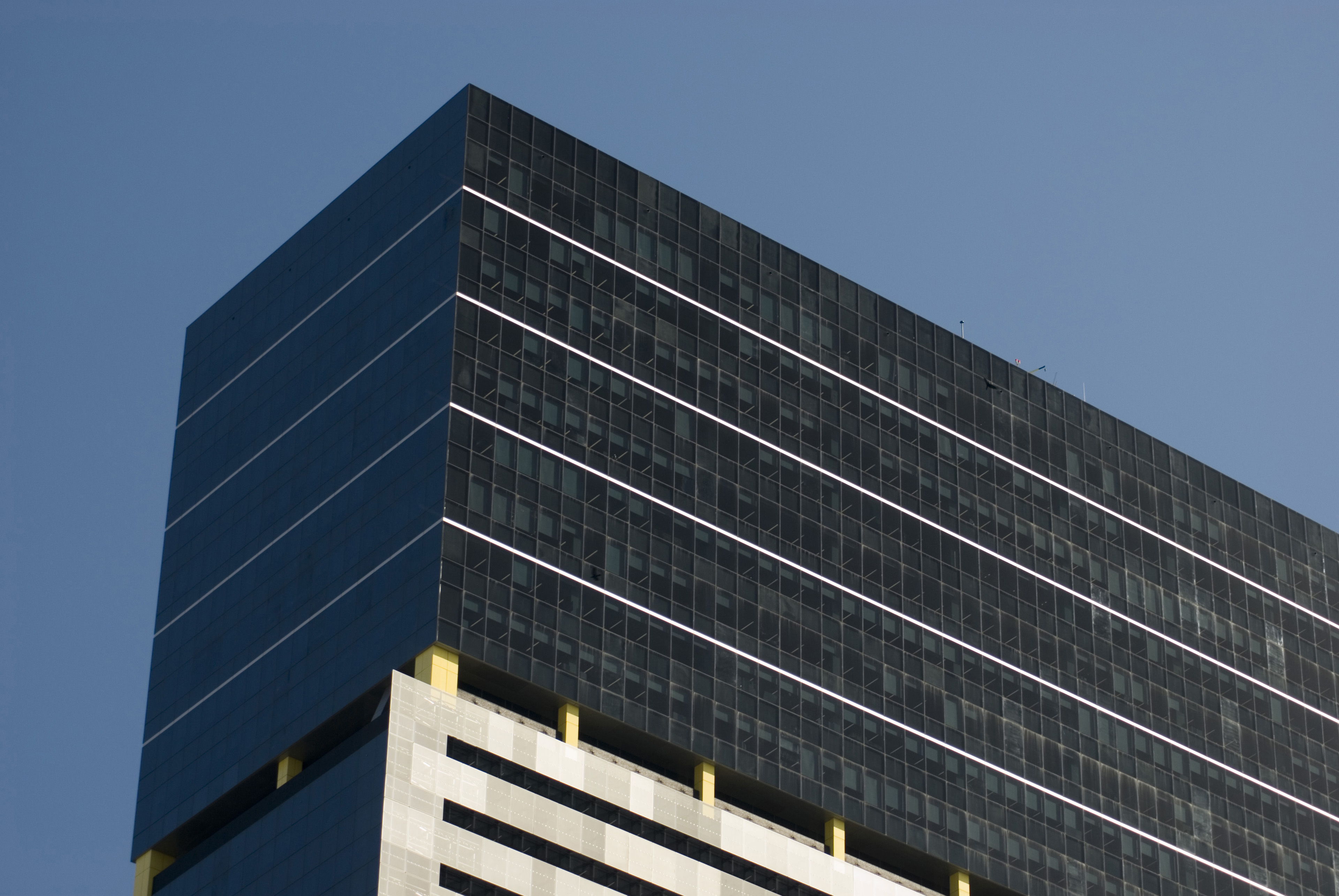 Top Part of Architectural Large Office Building with Glass Walls on Blue Gray Sky Background.
