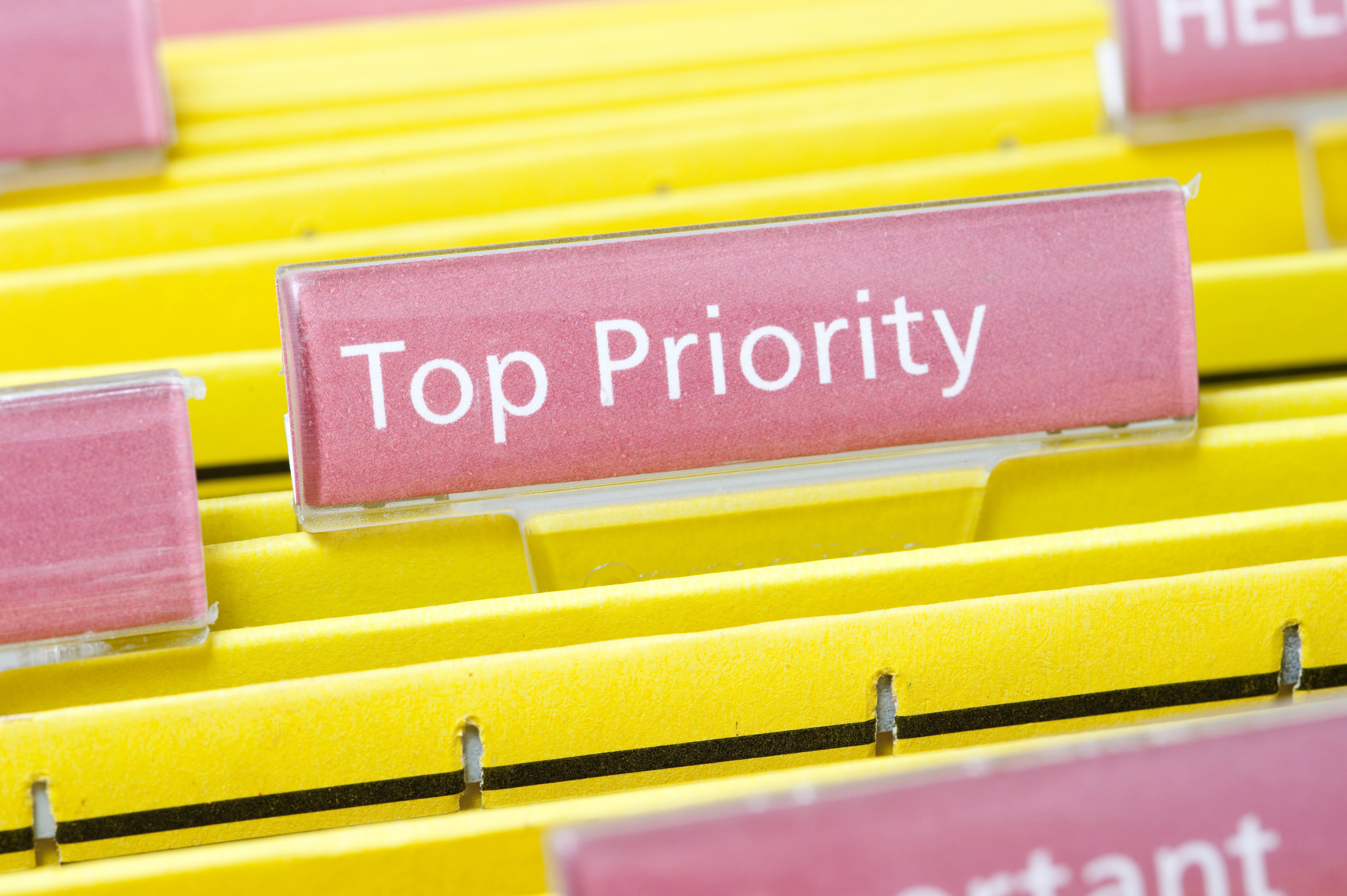 Priority Task Concept - Close up Yellow Folders with Pink Labels, Emphasizing Top Priority.