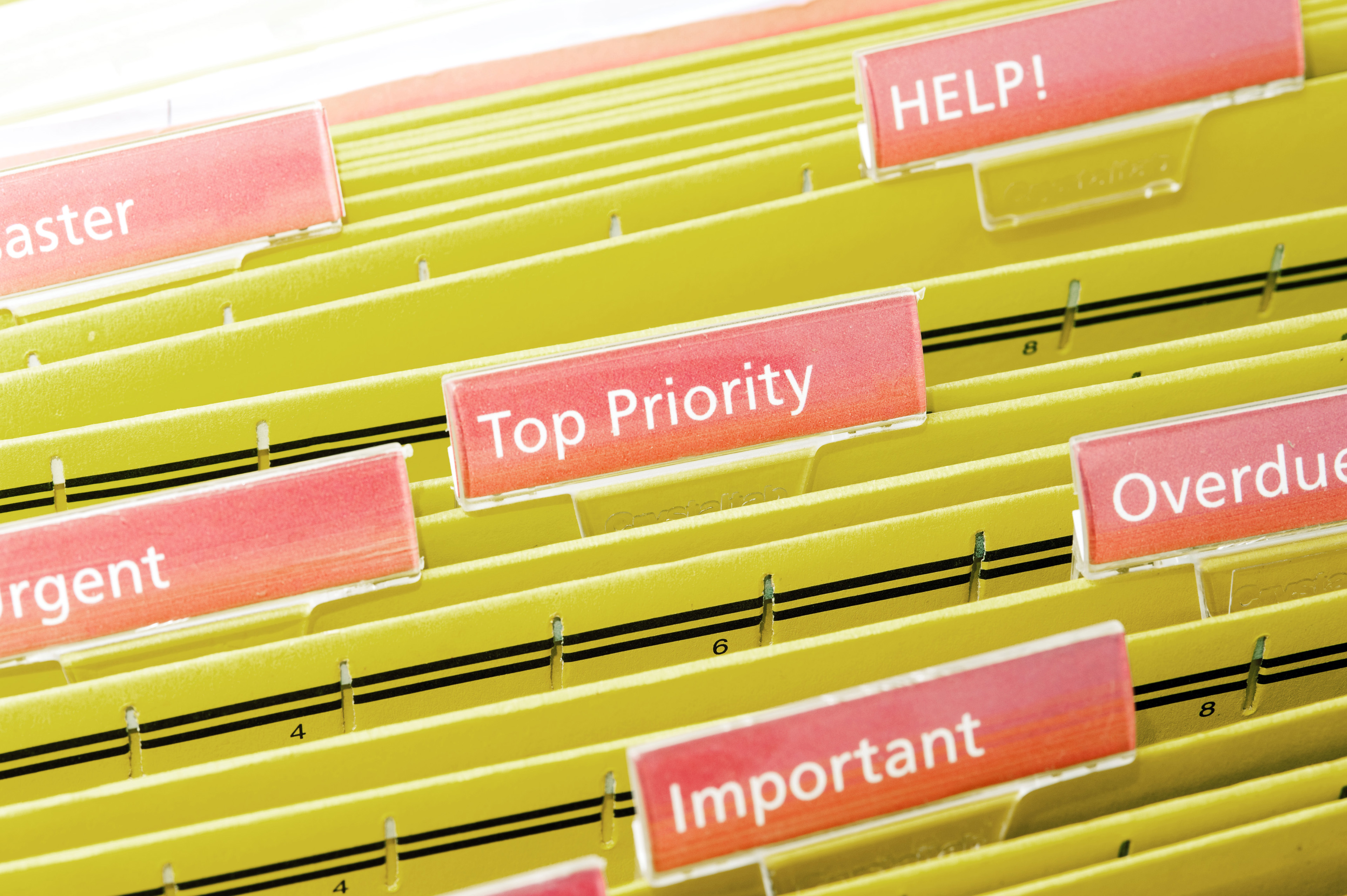 Urgent Tasks Concept - Priority Files on Yellow Folders Inside a Shelf with Pink Labels