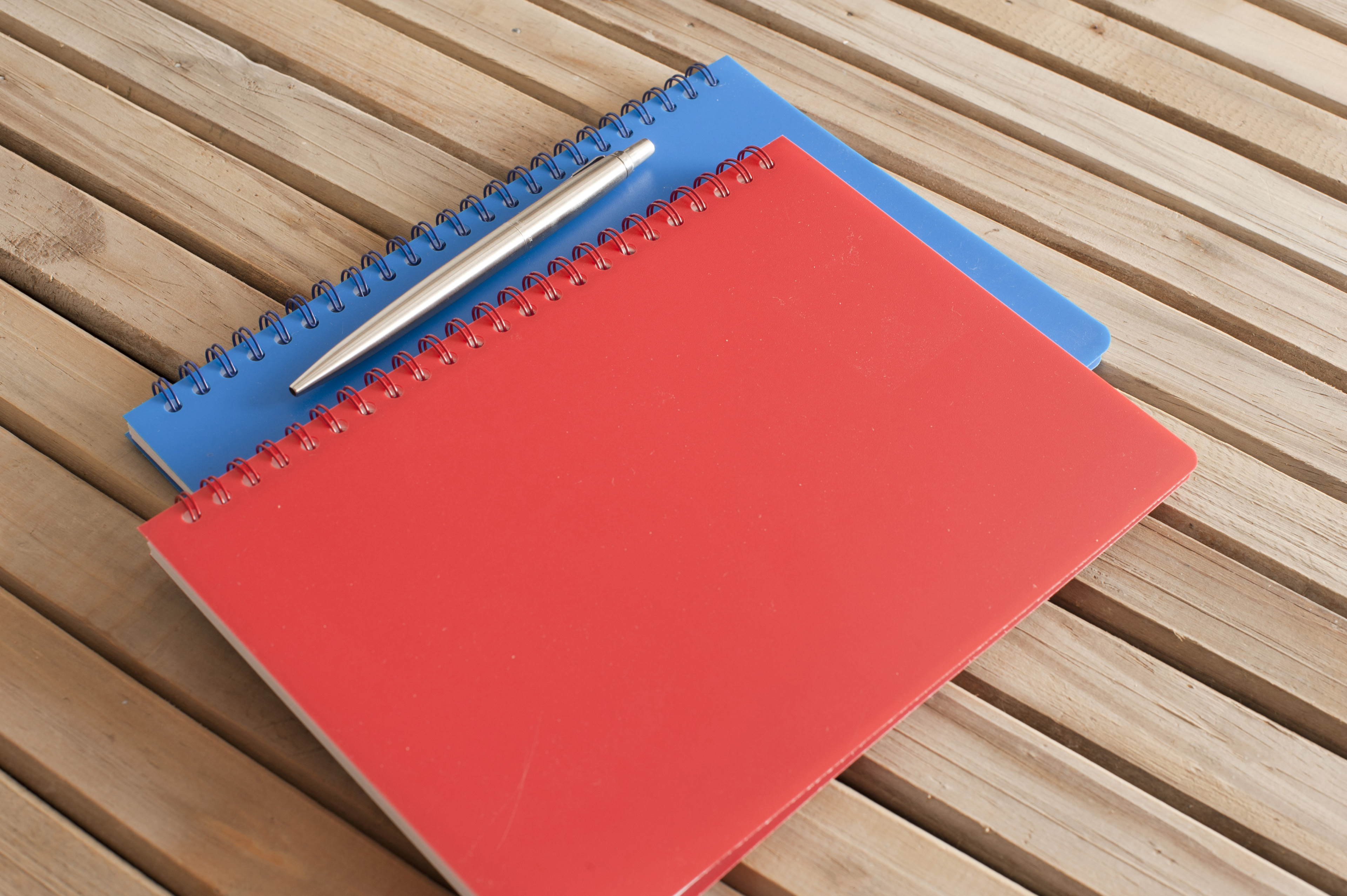Close up Closed Blue and Red Notebooks with Ballpoint Pen on Top Placed on Wooden Table.