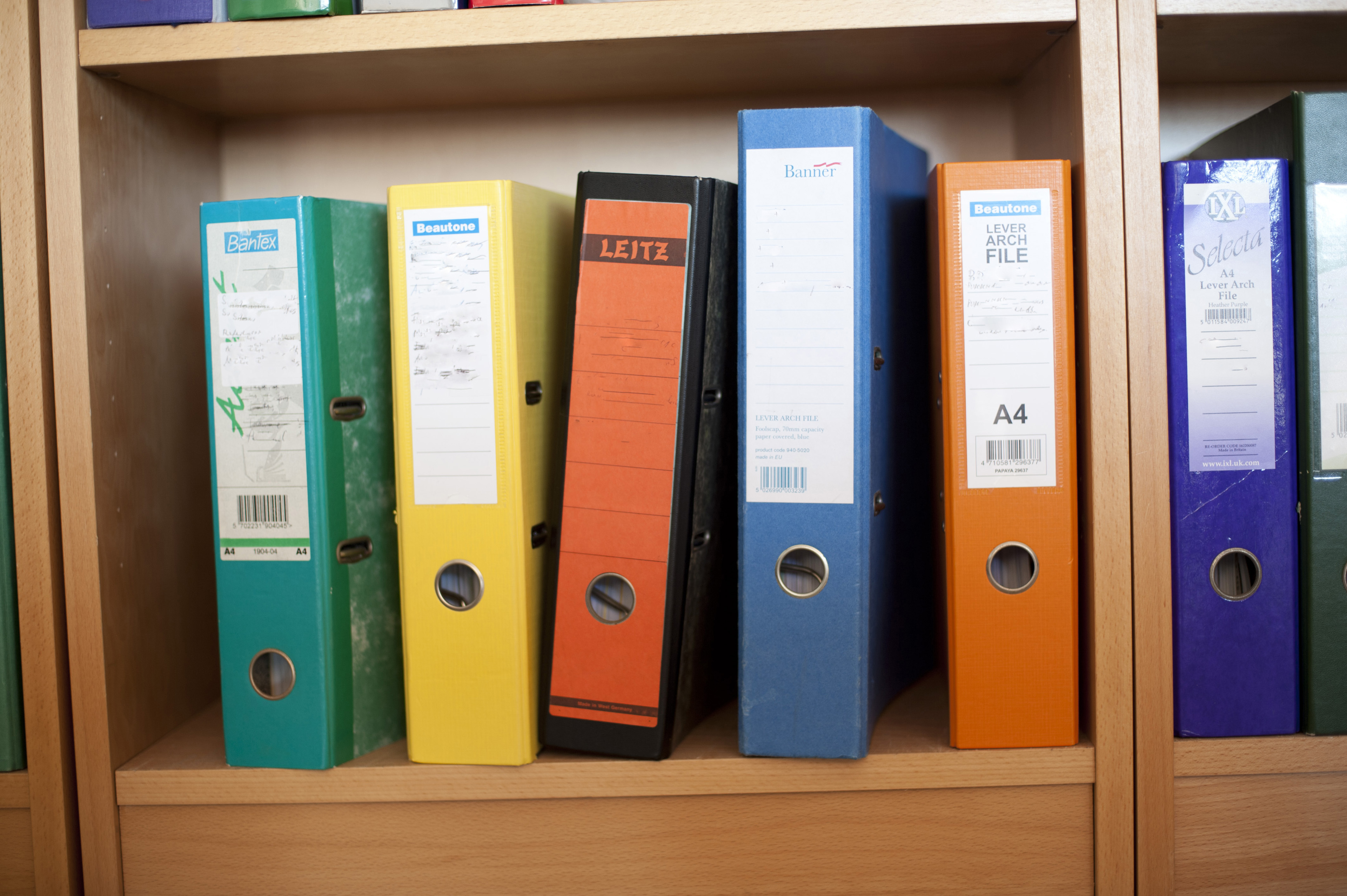Close up Assorted Colored Ring Binders of File on Wooden Cabinet at the Office.