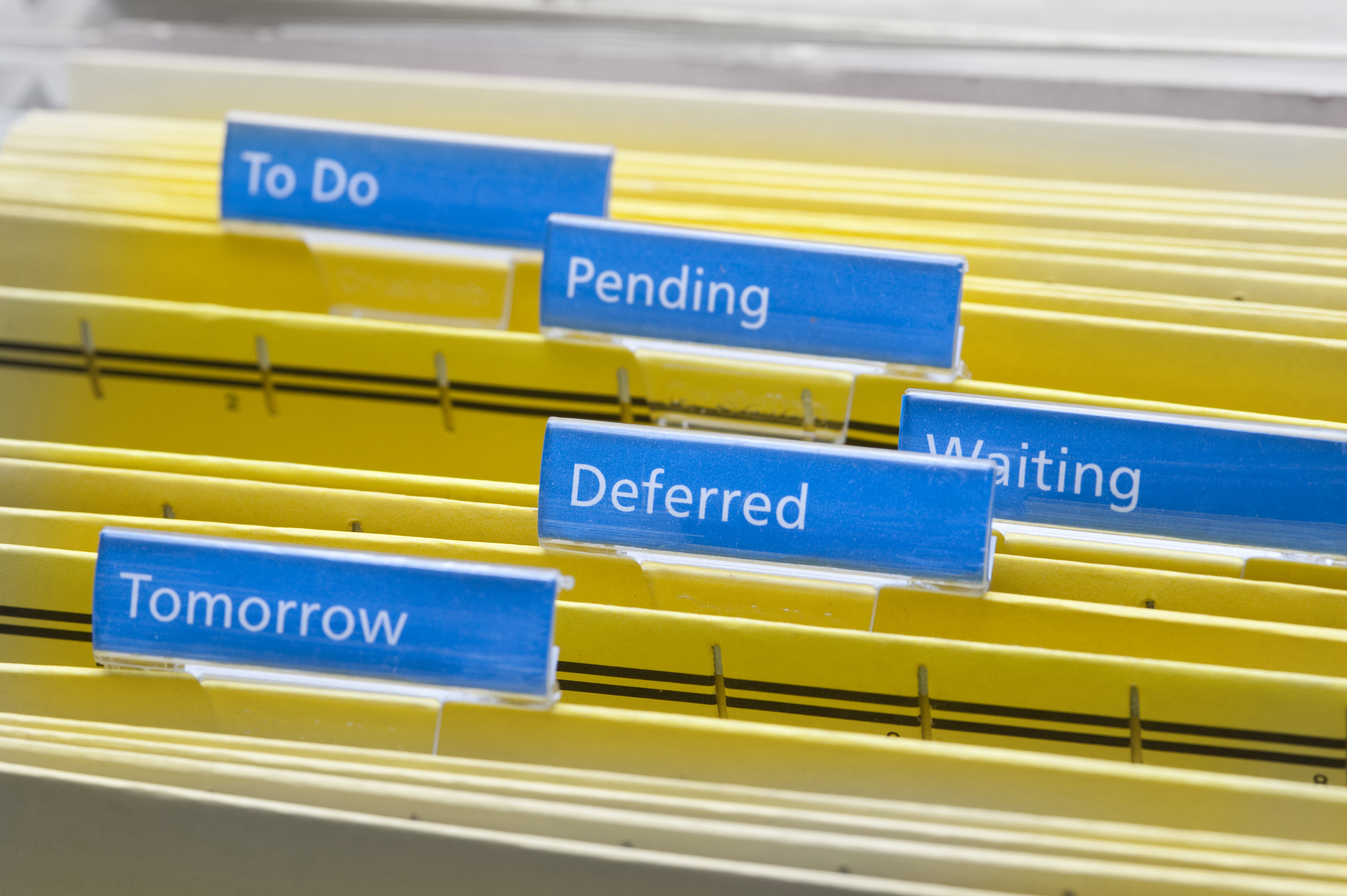 Close up Yellow Folders with Blue Labels for Work Procrastination Concept, Emphasizing To Do, Pending, Waiting, Deferred and Tomorrow Keywords.