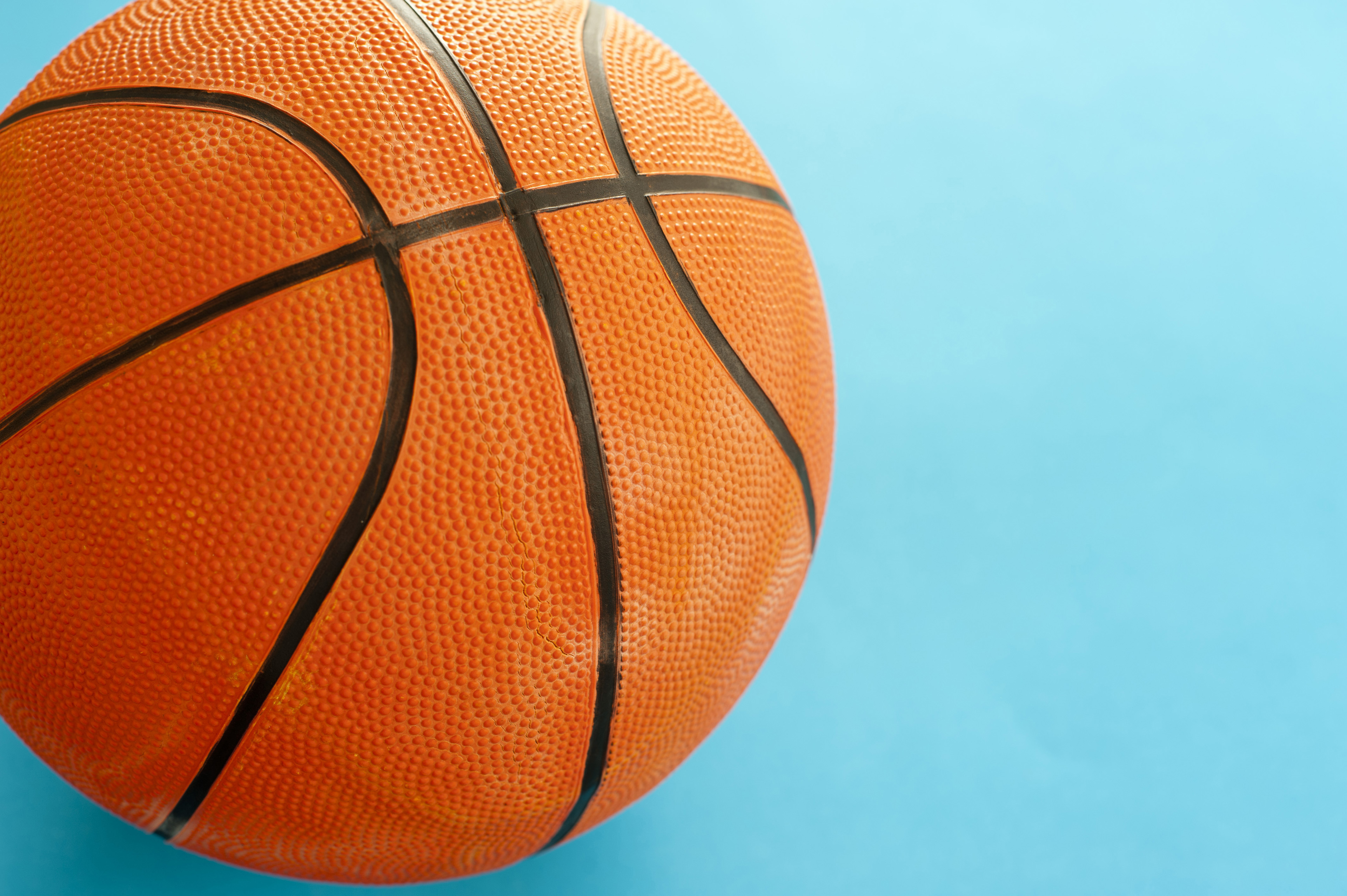 Close up One Orange Basketball Ball Isolated on Sky Blue Background with Copy Space for Texts