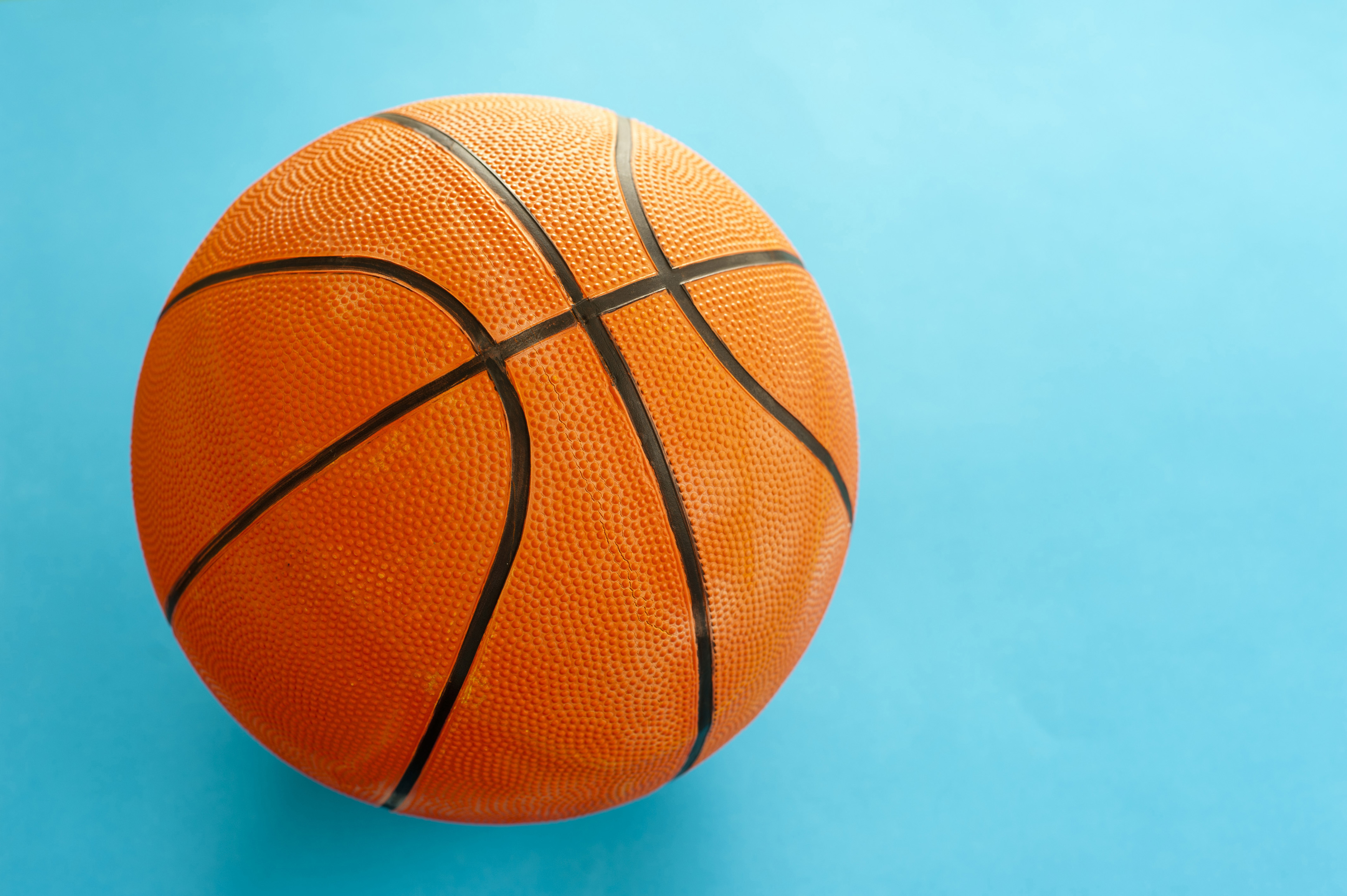 Colorful orange basketball isolated on a turquoise blue background with copyspace to the right in a sports concept