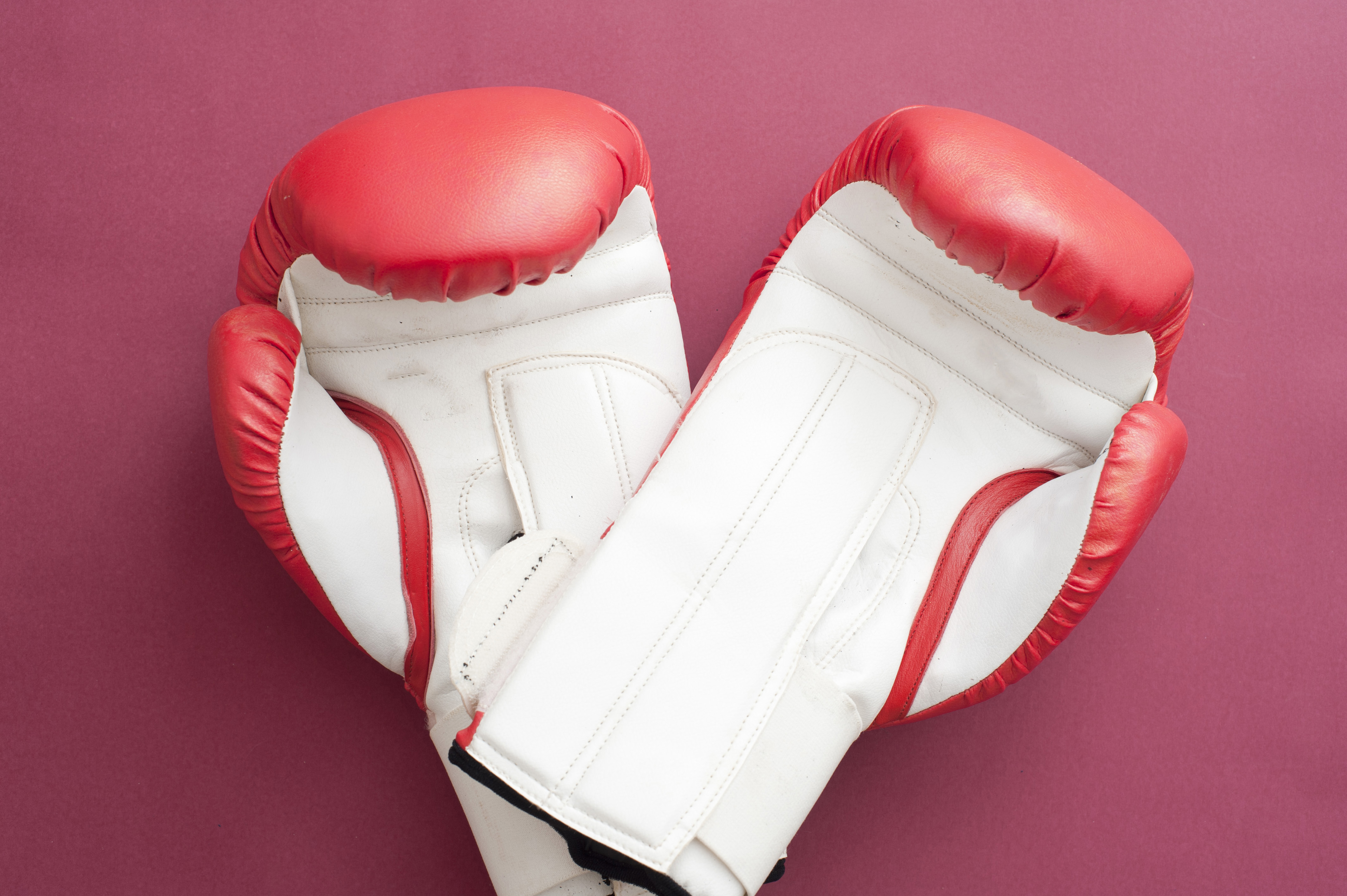Close up Pair of Red and White Boxing Gloves for Workout Isolated on a Fuchsia Background