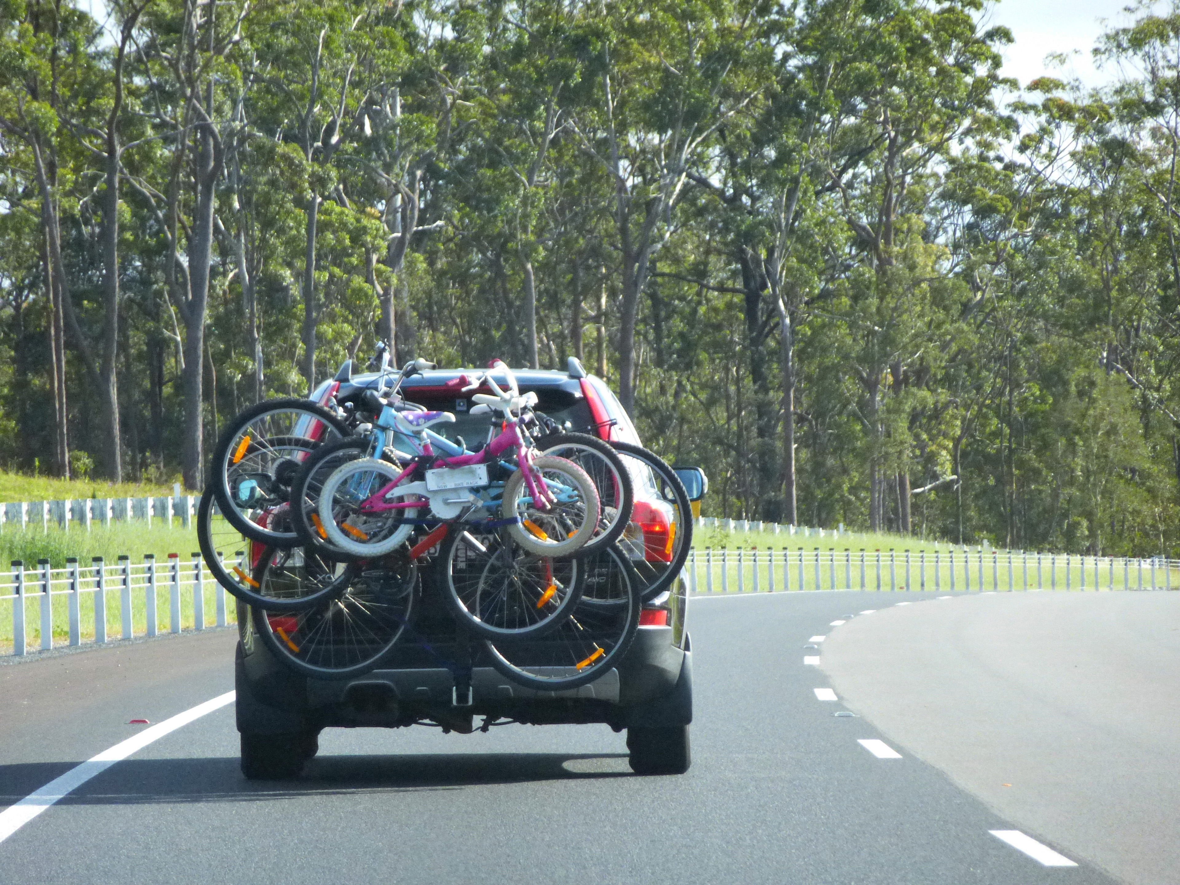 Car transporting bicycles for a cycle tour or weekend family outing with bicycles of all sizes strapped to the carrier as it travels along the motorway