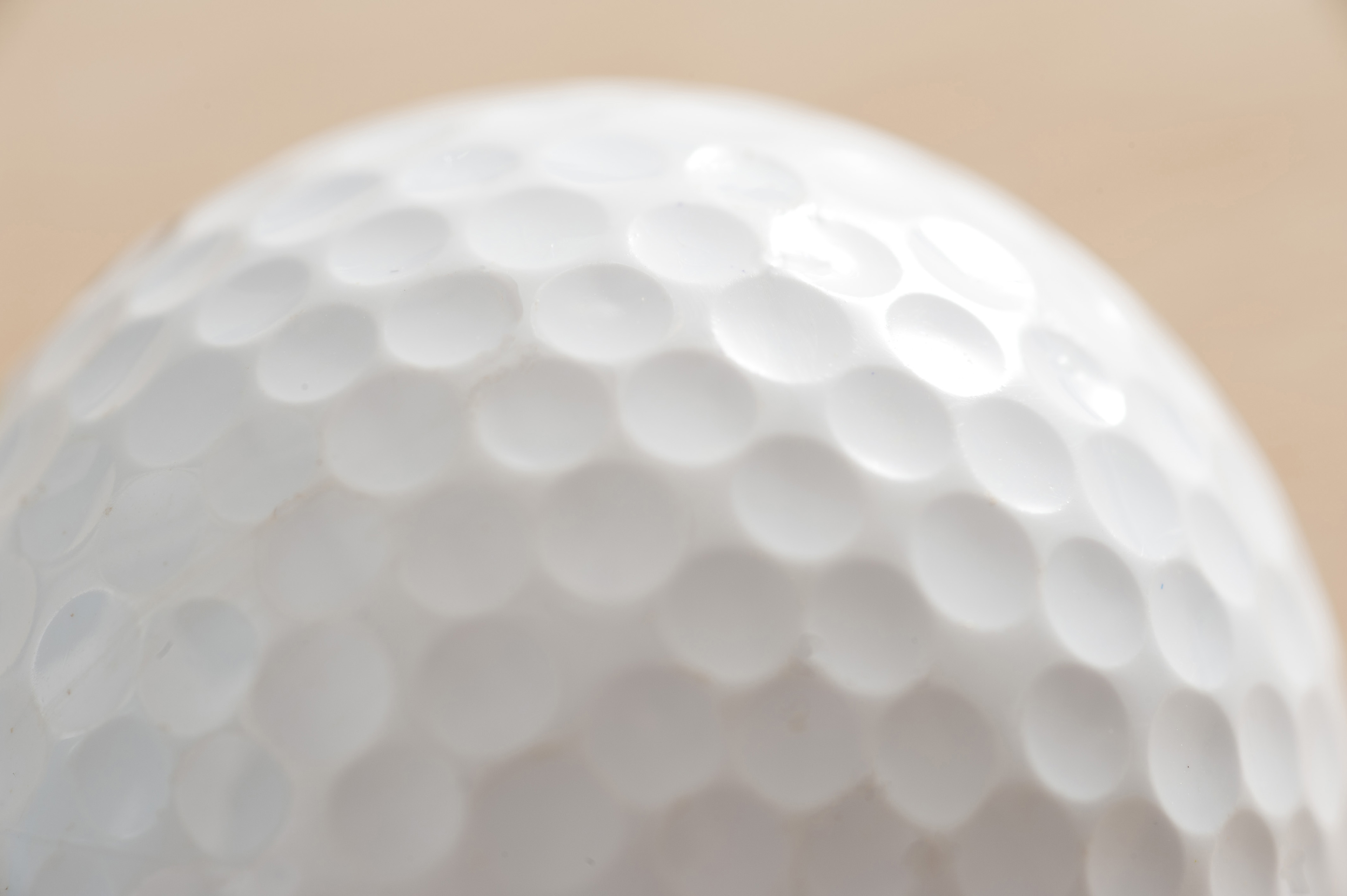 Close up detail of a white golf ball showing the dimpled texture of the surface in a golfing or sporting concept