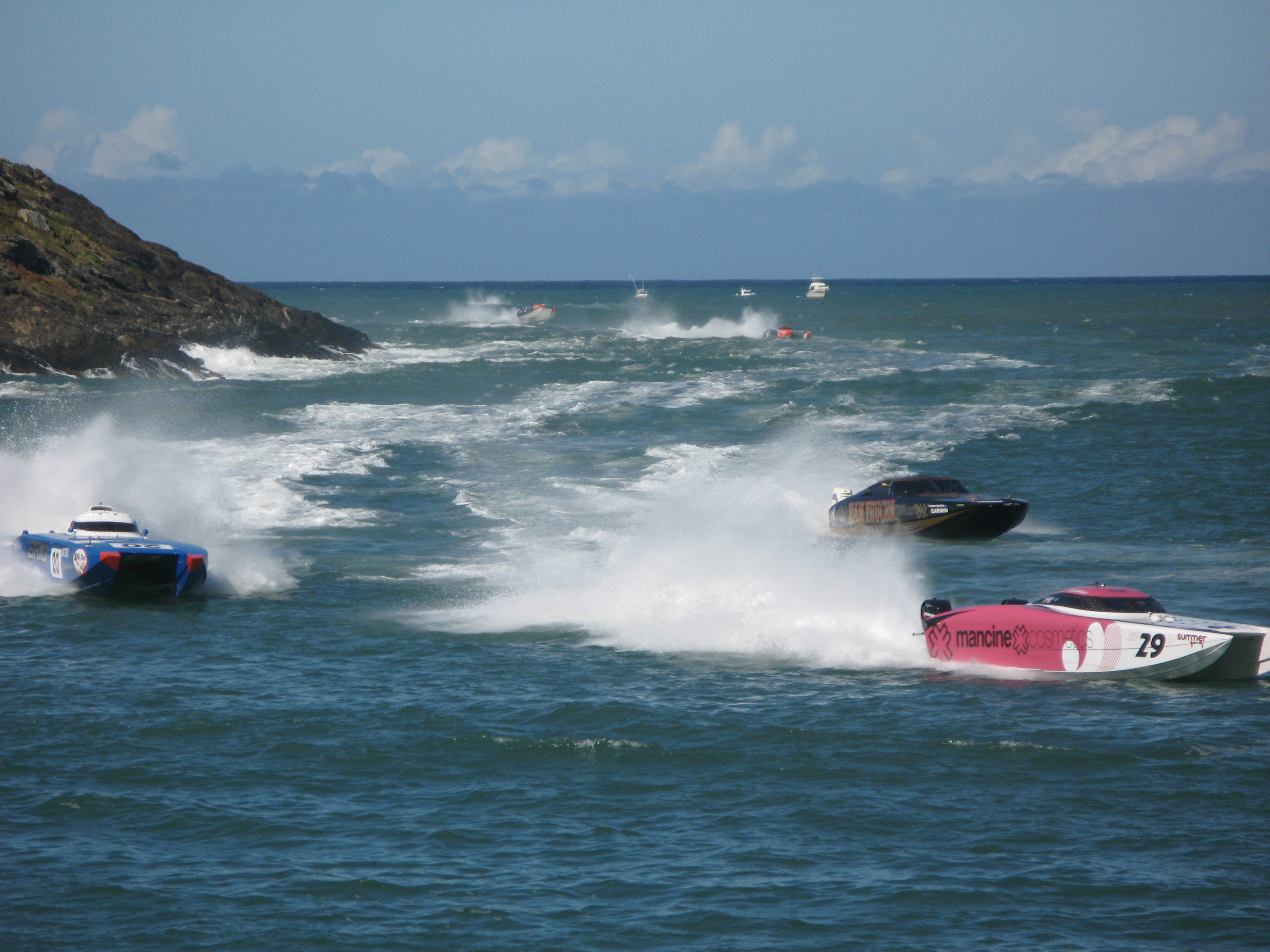 Jet boats racing offshore in a power boat race speeding through the water in a cloud of spray