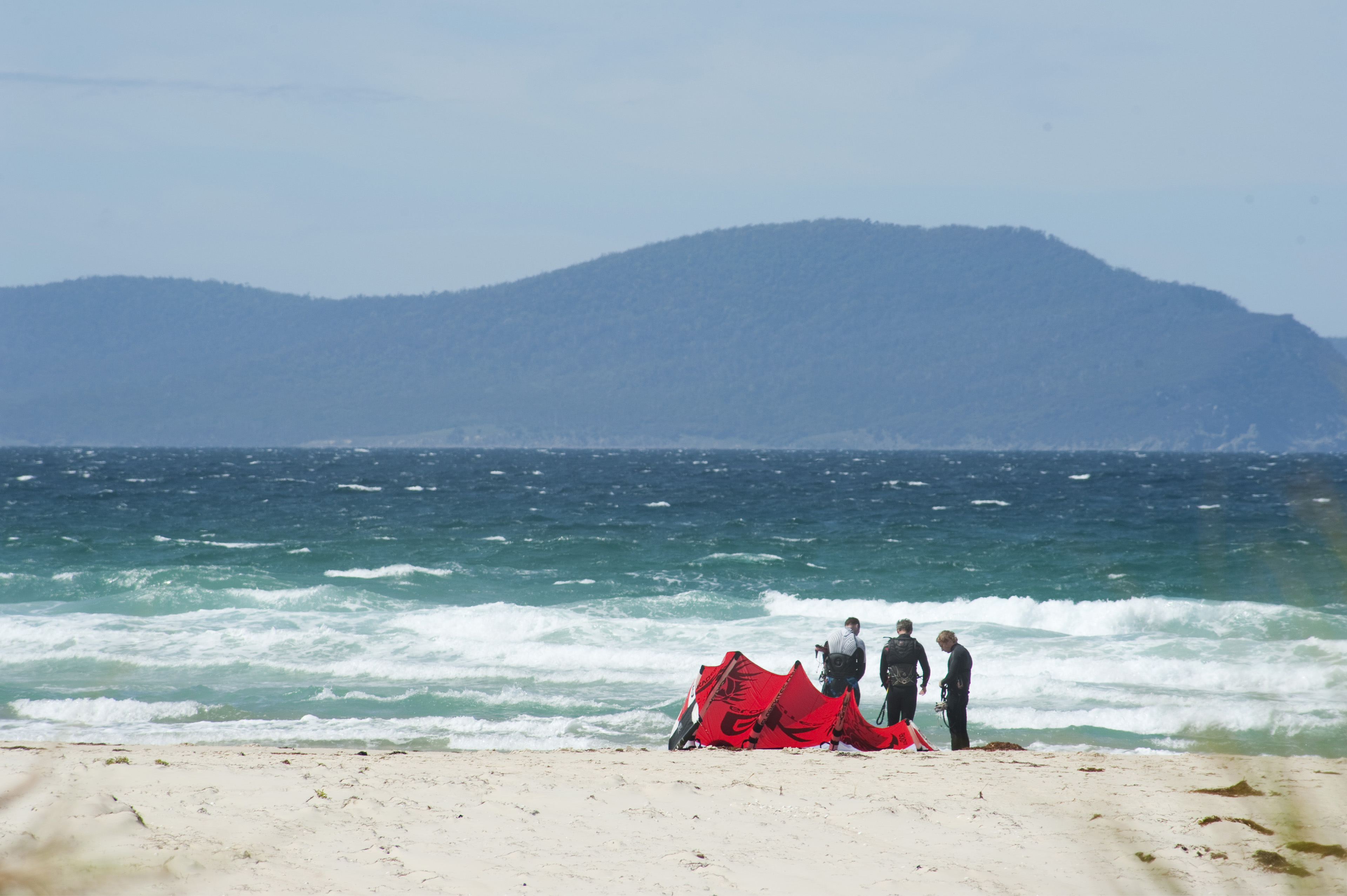 Kite surfers preparing their kite board on a sandy tropical beach with a wind swept ocean and mountain backdrop