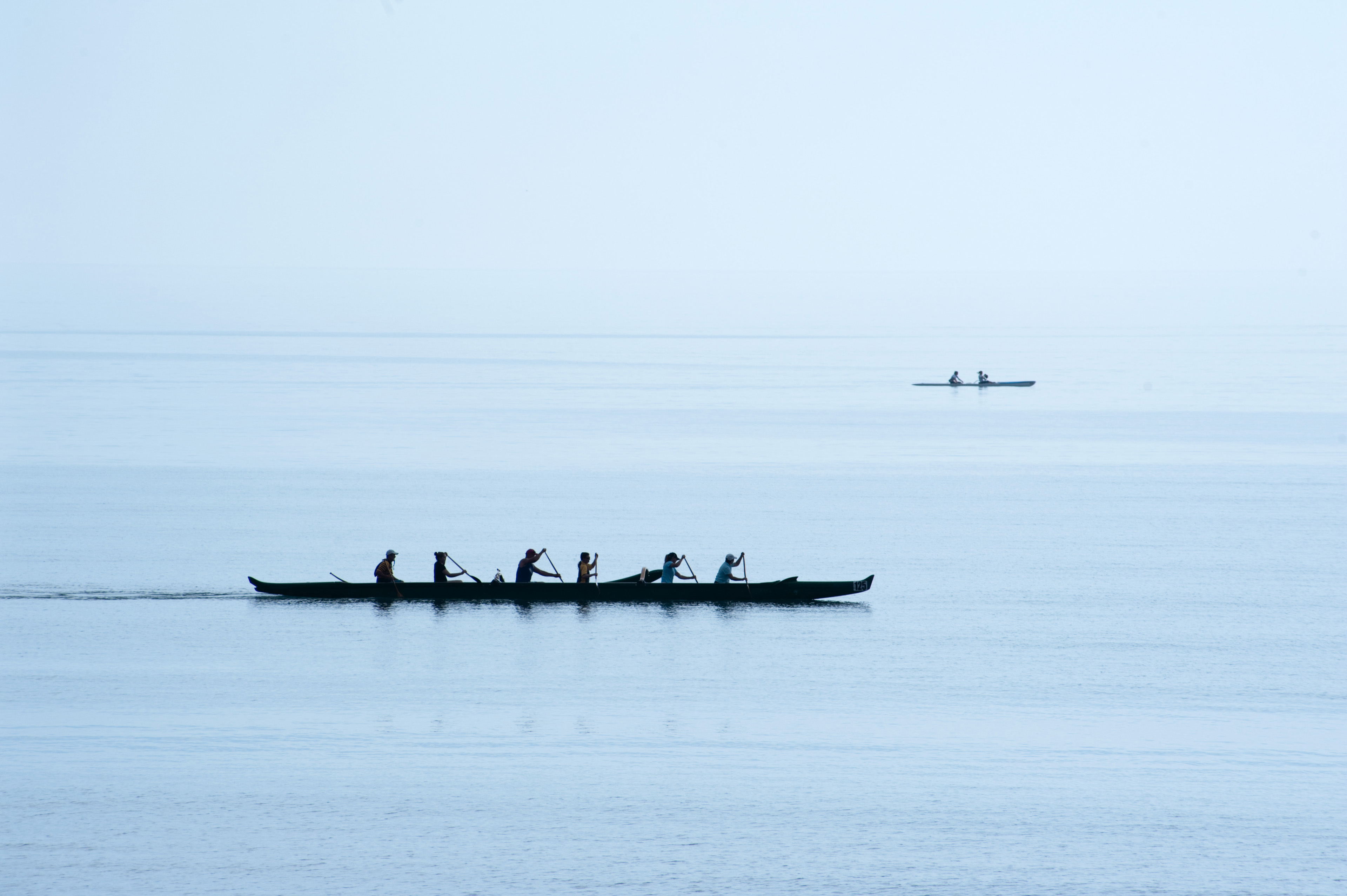 Team of rowers competing in a race in a six man canoe silhouetted against a calm ocean as they paddle furiously to gain speed