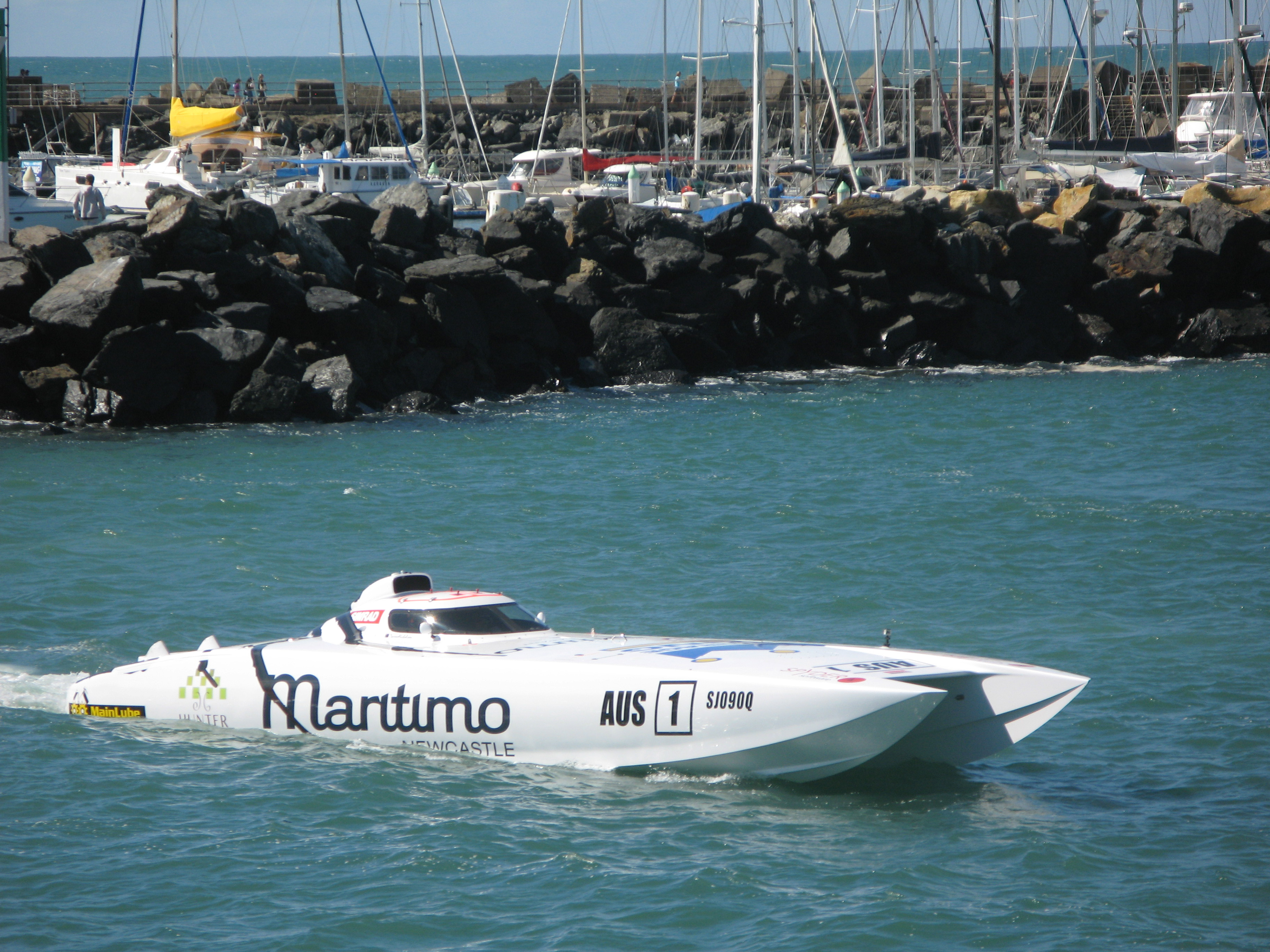 A competitor in power boat racing idling his speedboat in front of a harbor wall as he waits for his race