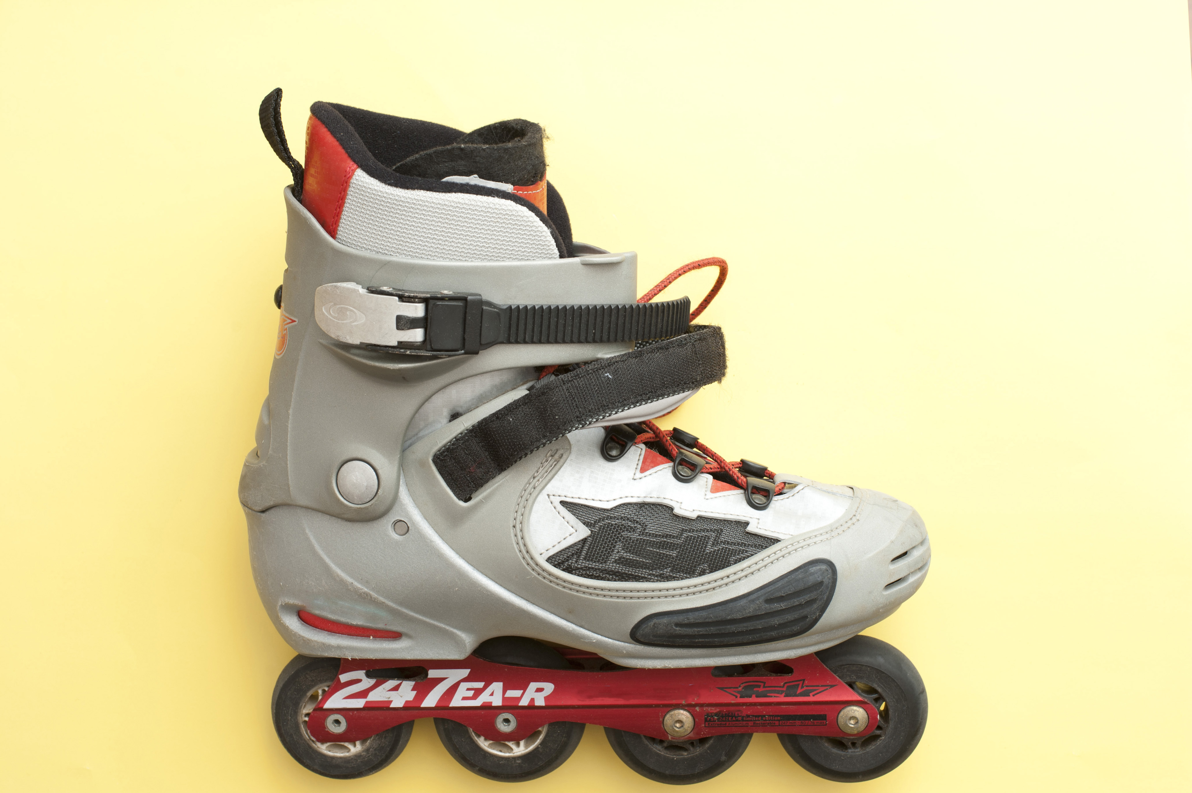 Modern inline roller skate or roller blade with four wheels aligned in a row on a yellow background with copyspace