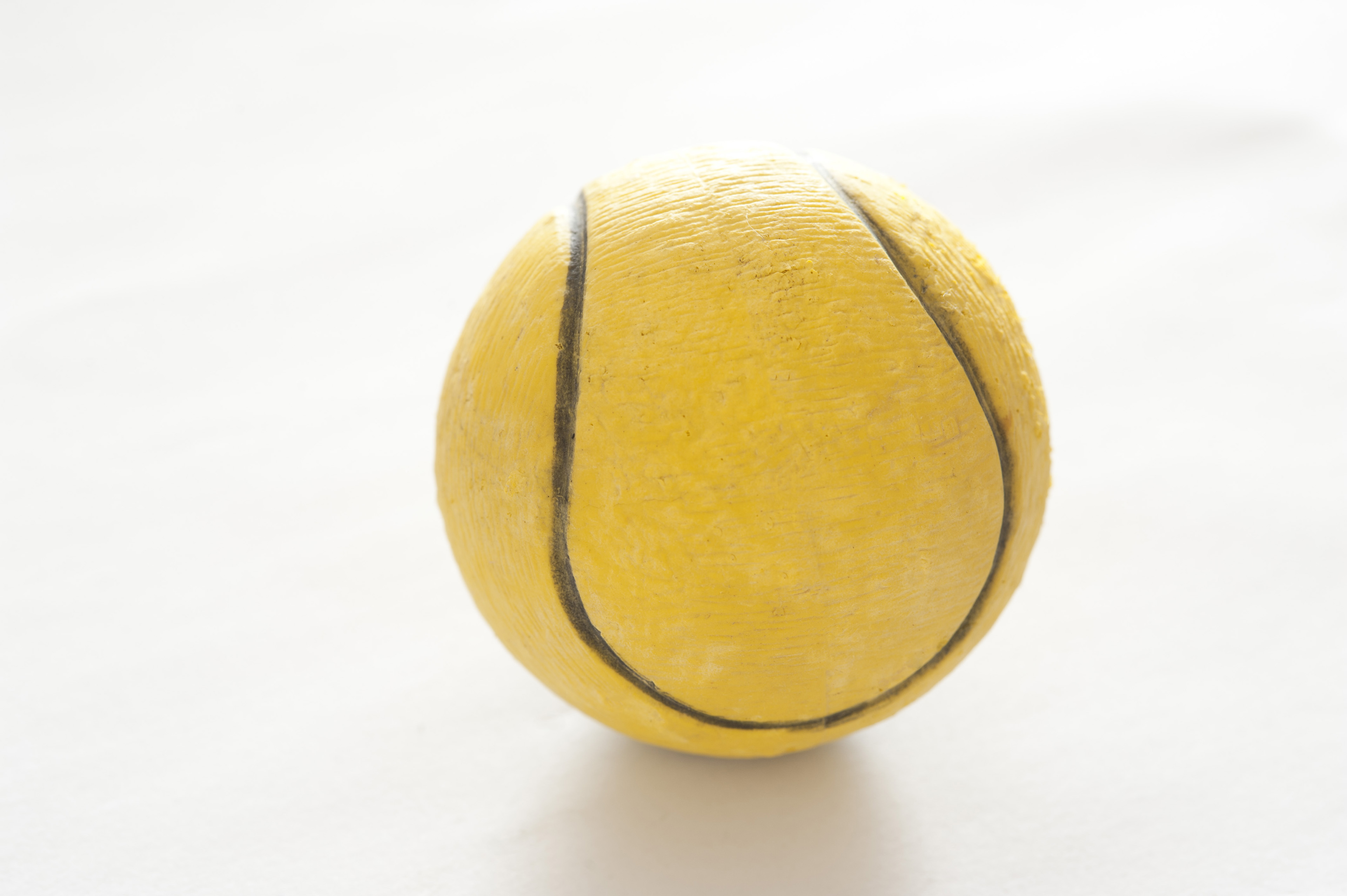 Used yellow rubber tennis ball for playing on a court backlit on a white background, close up view