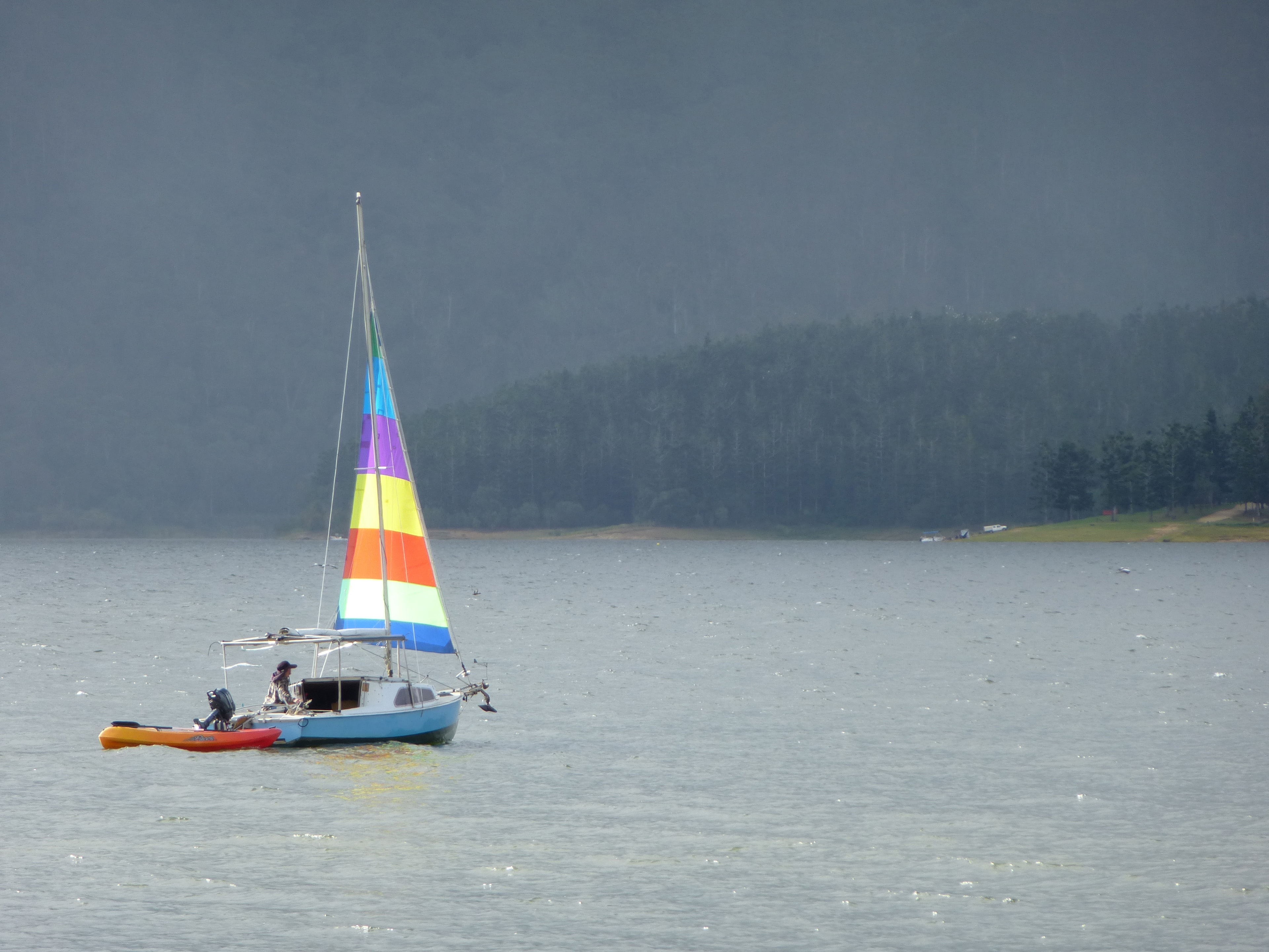 Small sailboat with a single colourful sail towing a dinghy offshore on a misty cold day with the coastline visible in the distance