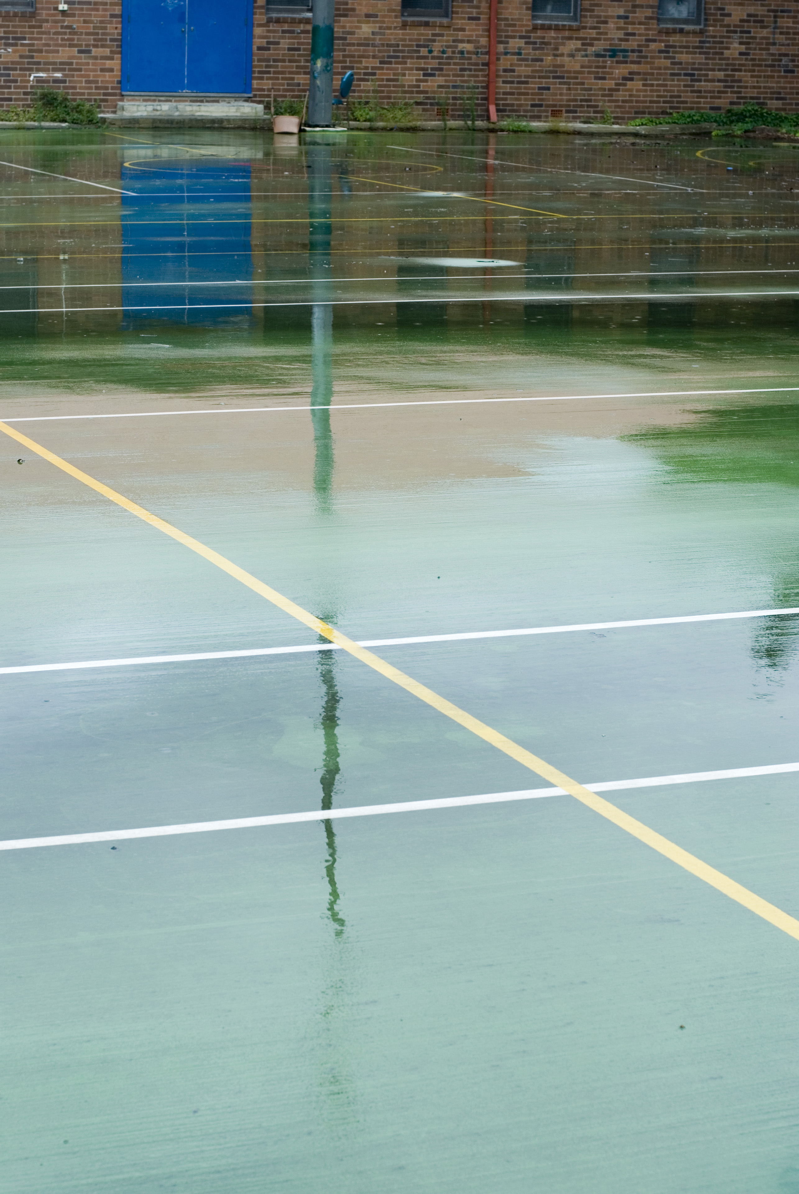 Wet green surface of an all-weather sports court with reflections of the poles and painted lines in an urban or school environment