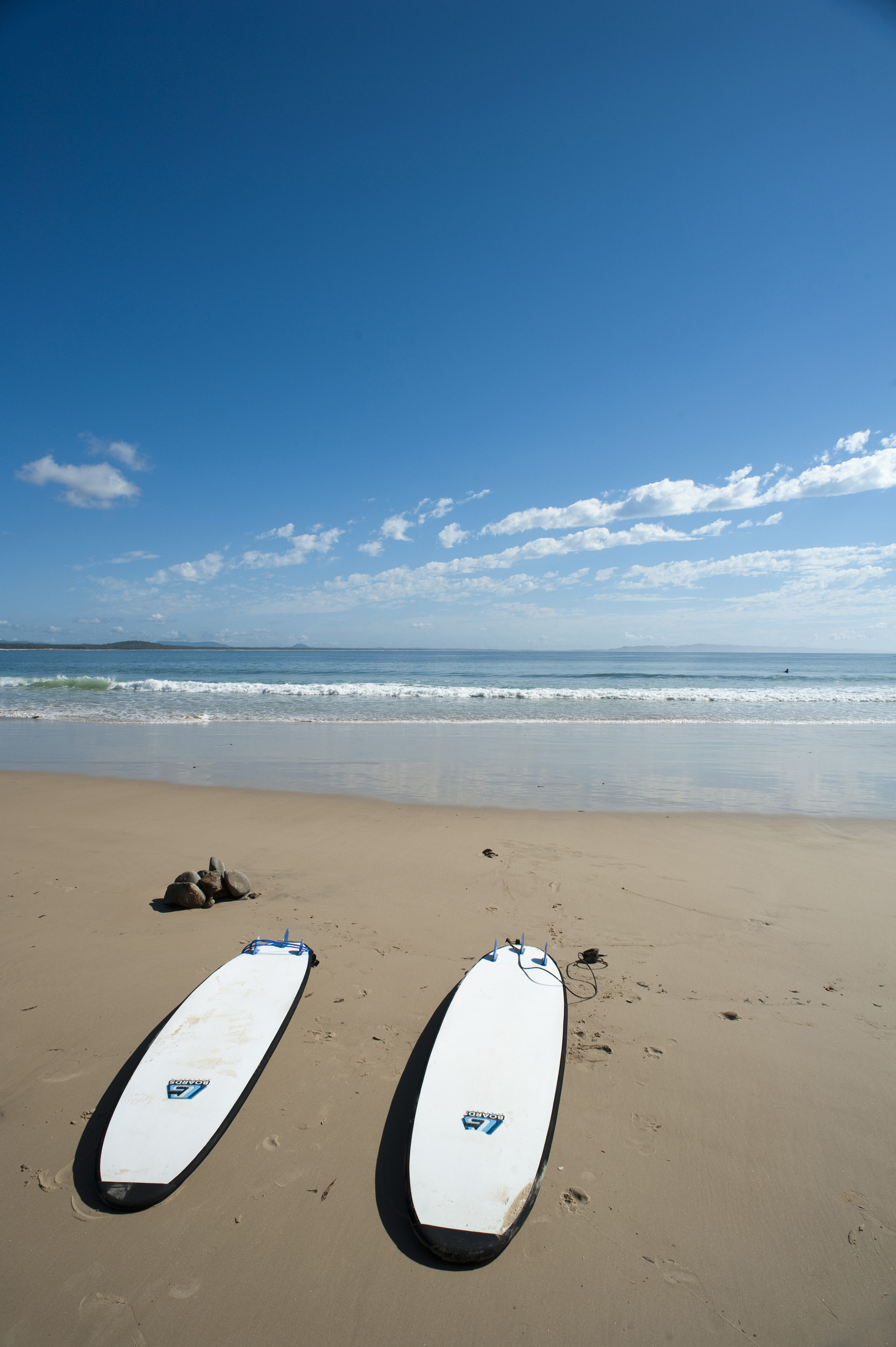 Two White Surfboards on Sandy Shore of Deserted Beach with Blue Sky