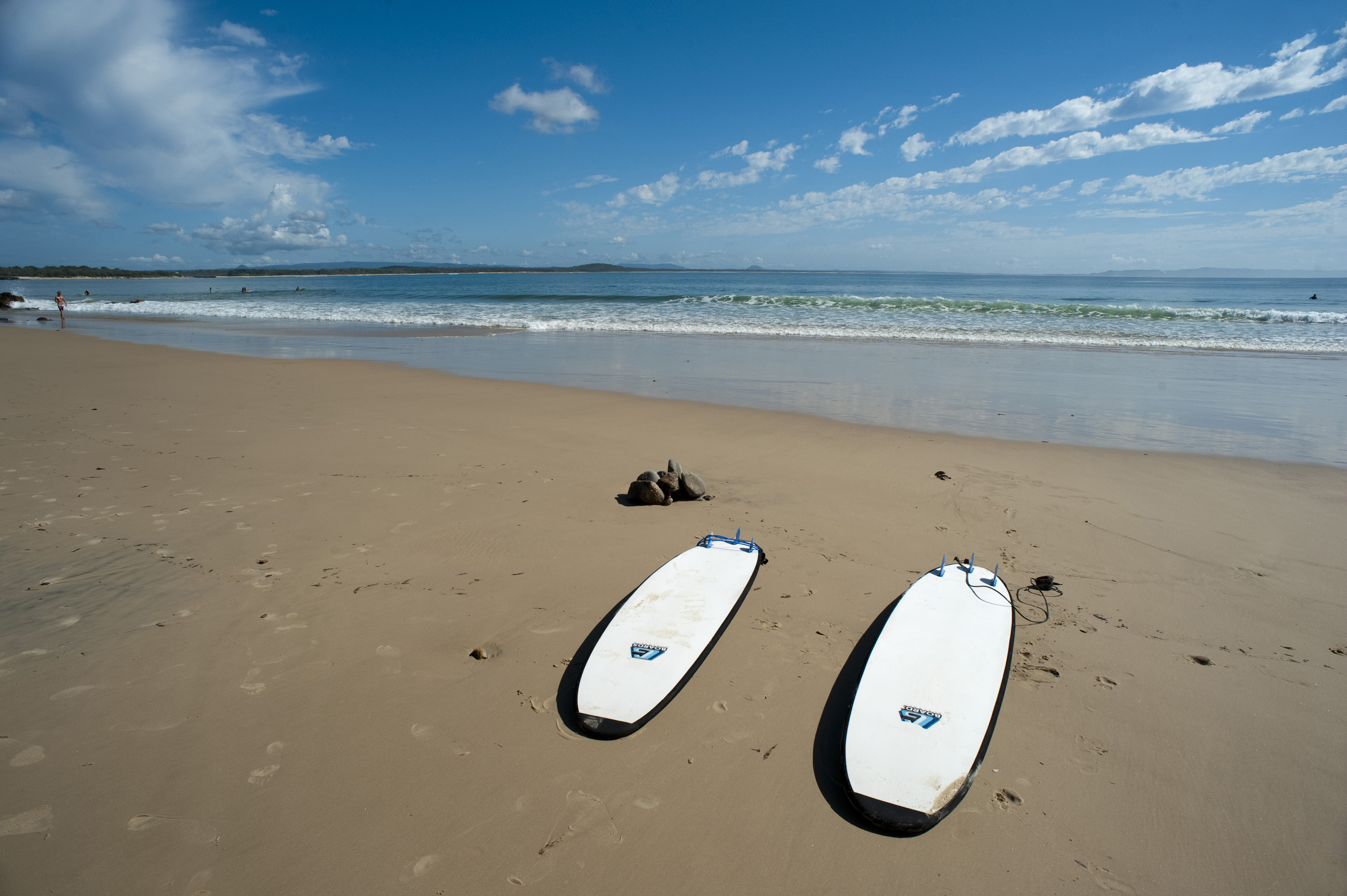 Surfing on a tropical beach concept with two surfboards left lying on the wet sand in front of a calm ocean, with copy space