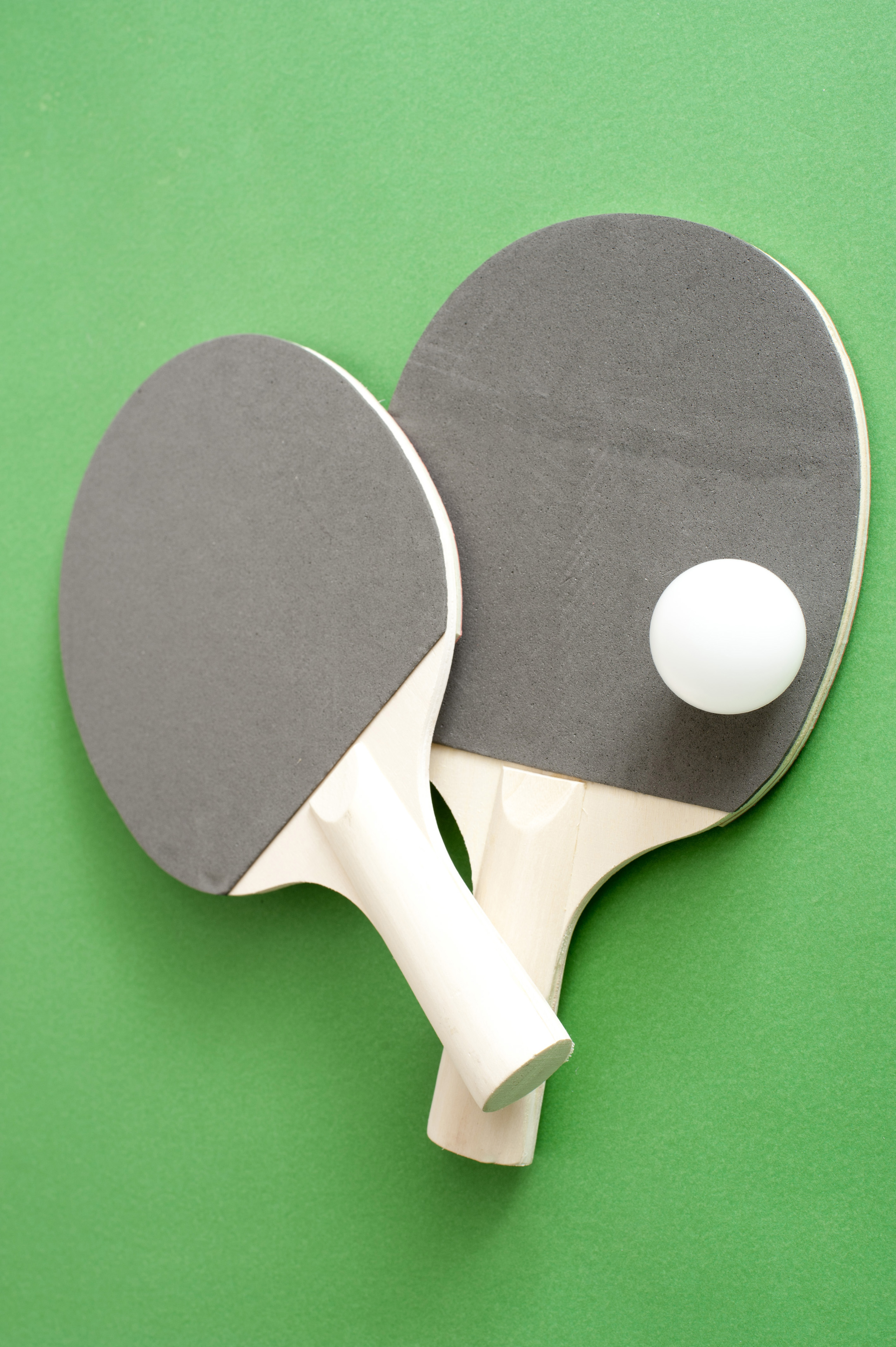 Table tennis bats and a ball lying on the green wooden table read for a game of indoor ping pong or table tennis