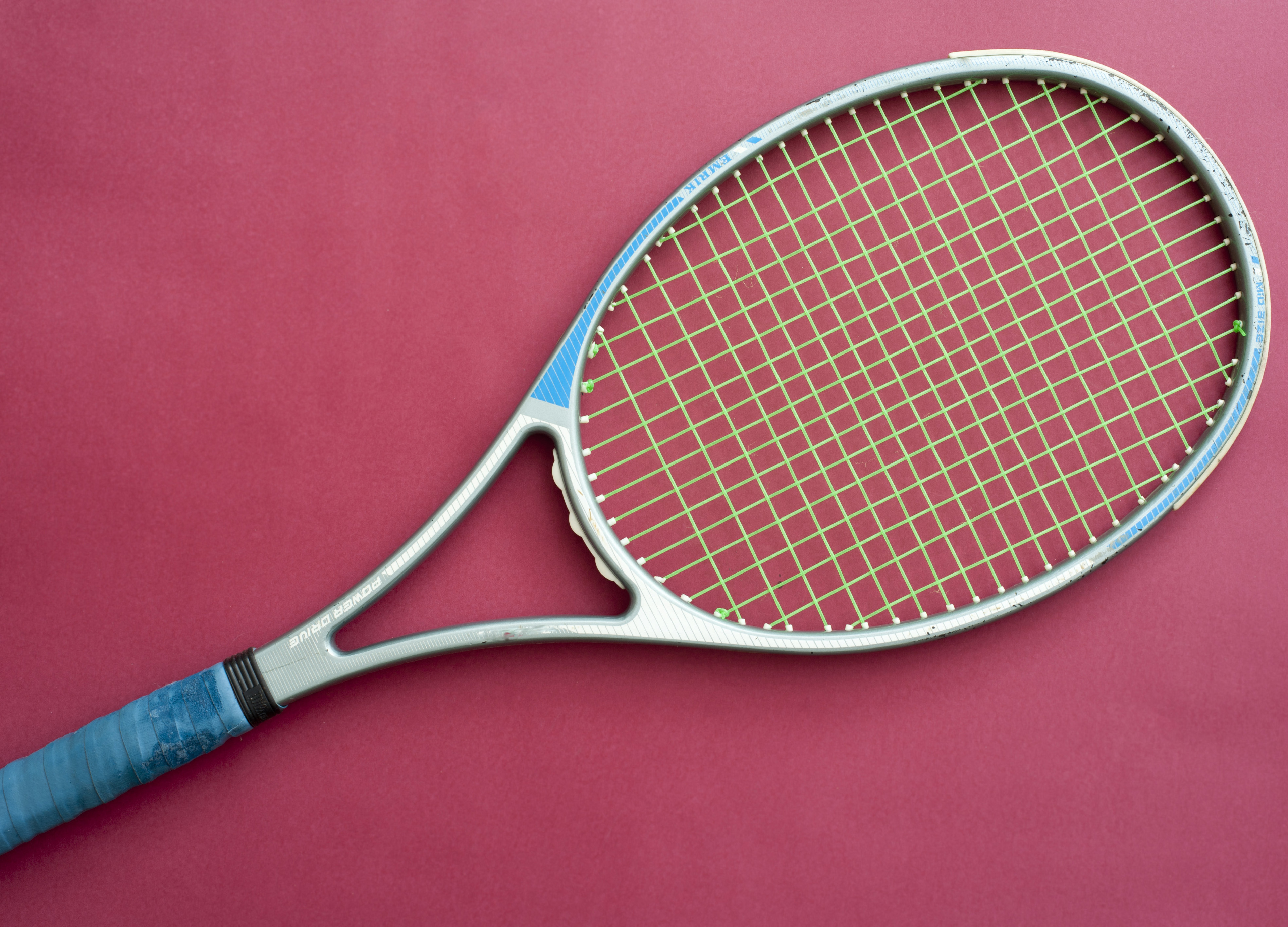 Modern metal frame tennis racket lying diagonally across the frame on a magenta background showing string detail