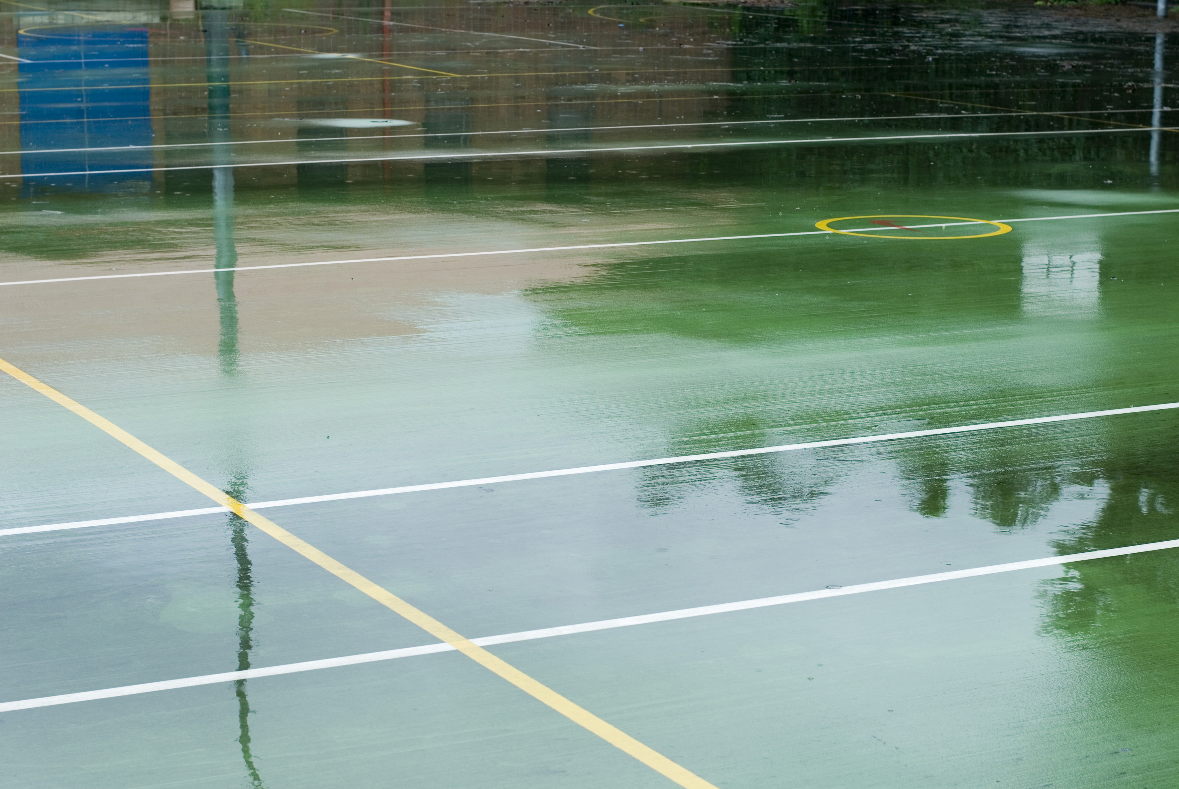 Wet outdoor all-weather sports court with yellow and white lines on a green surface reflecting surrounding trees on the surface of the water