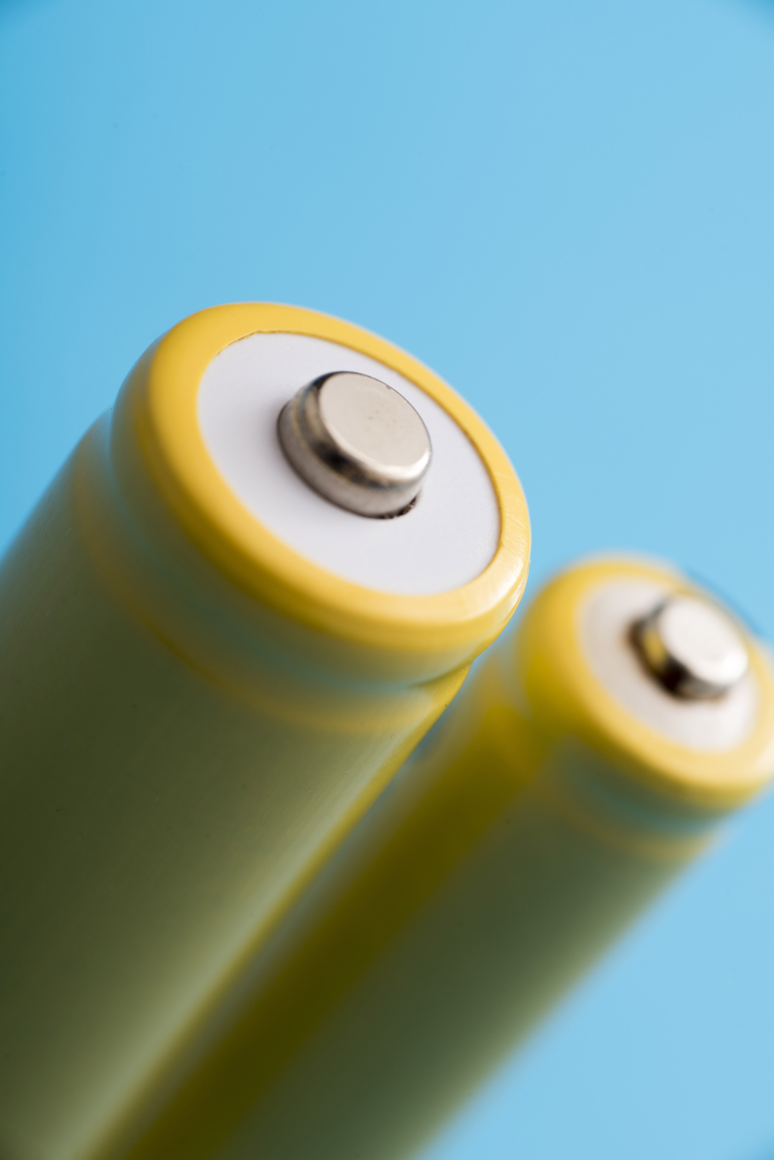 Close up view of the positive terminal on a rechargeable battery over a blue background in a power and energy concept