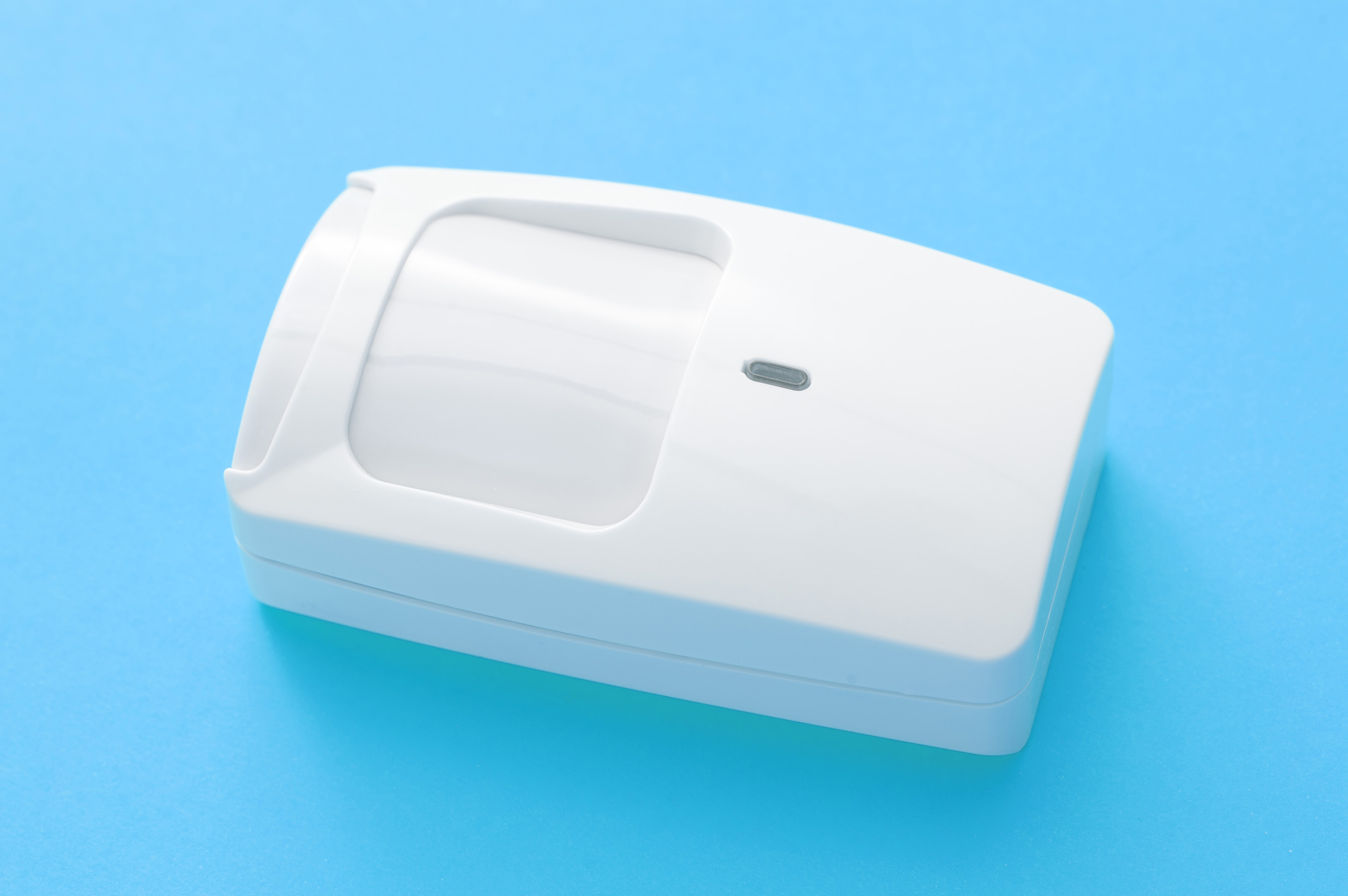 White plastic infrared motion sensor for an alarm system for a building interior lying on a turquoise blue background