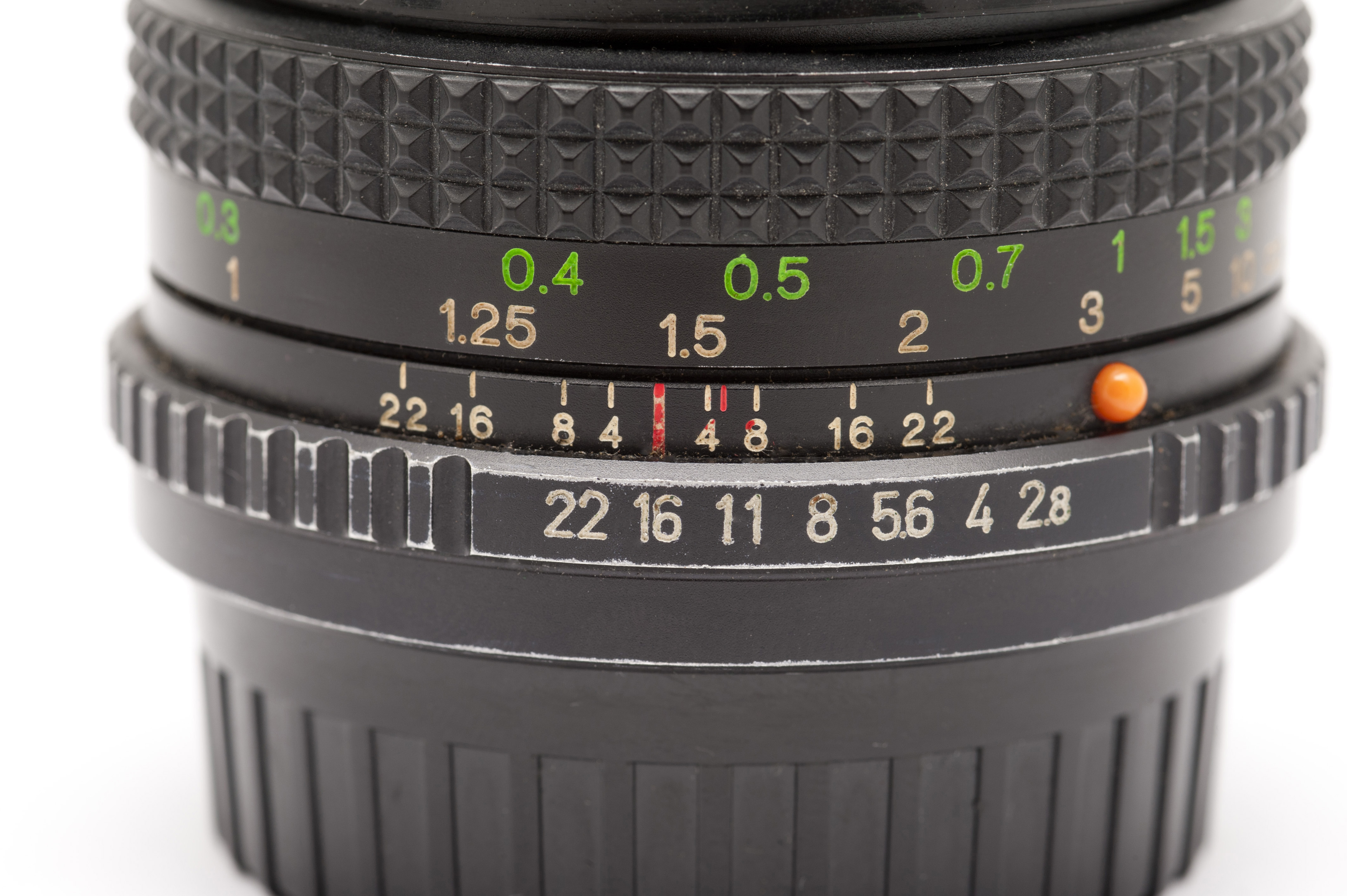 Close Up of Manual SLR Camera Lens with Aperture and Focal Length Setting Numbers in front of White Background