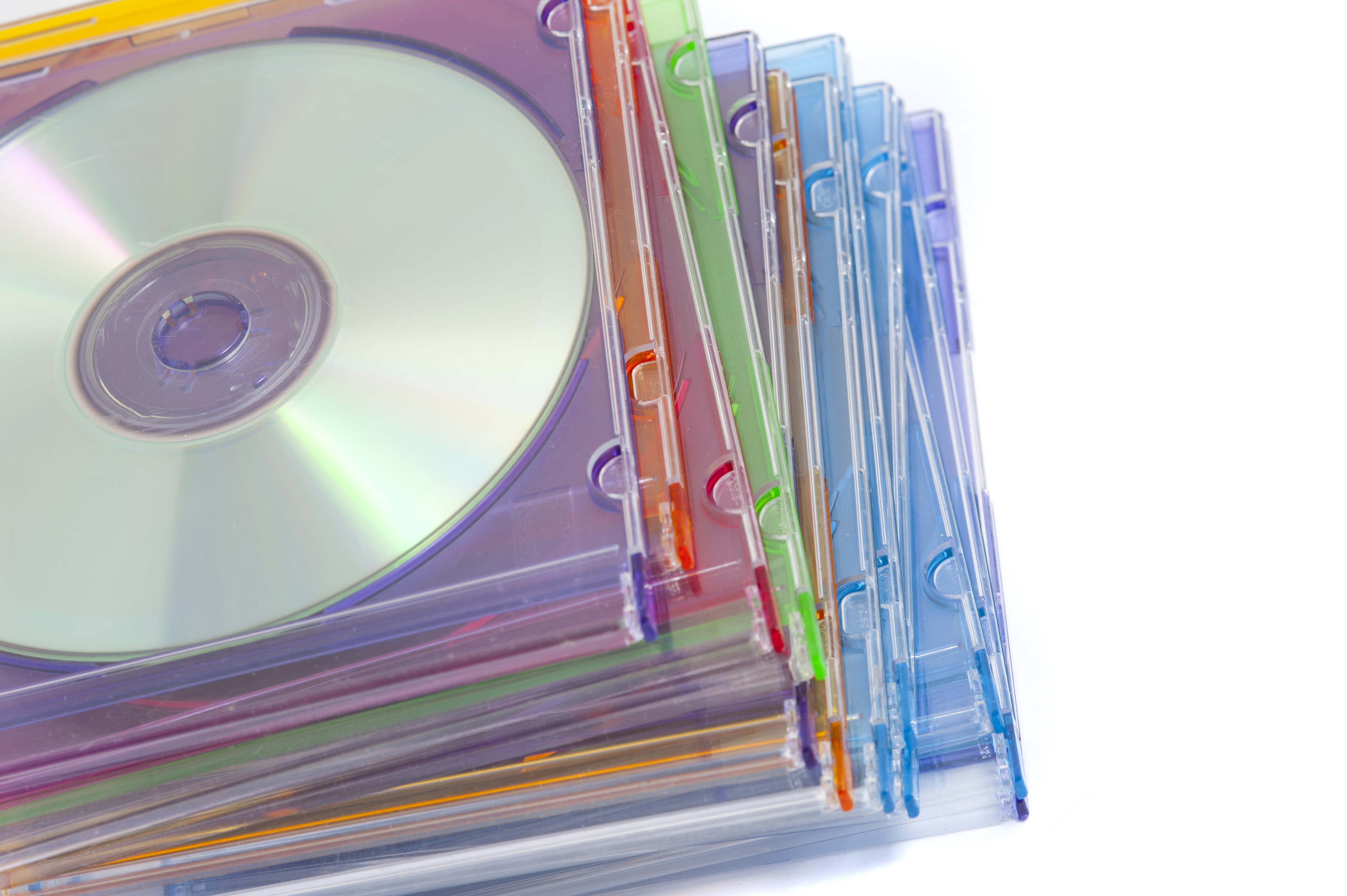 Close up Piled of Colored Compact Disc Cases on White Background.