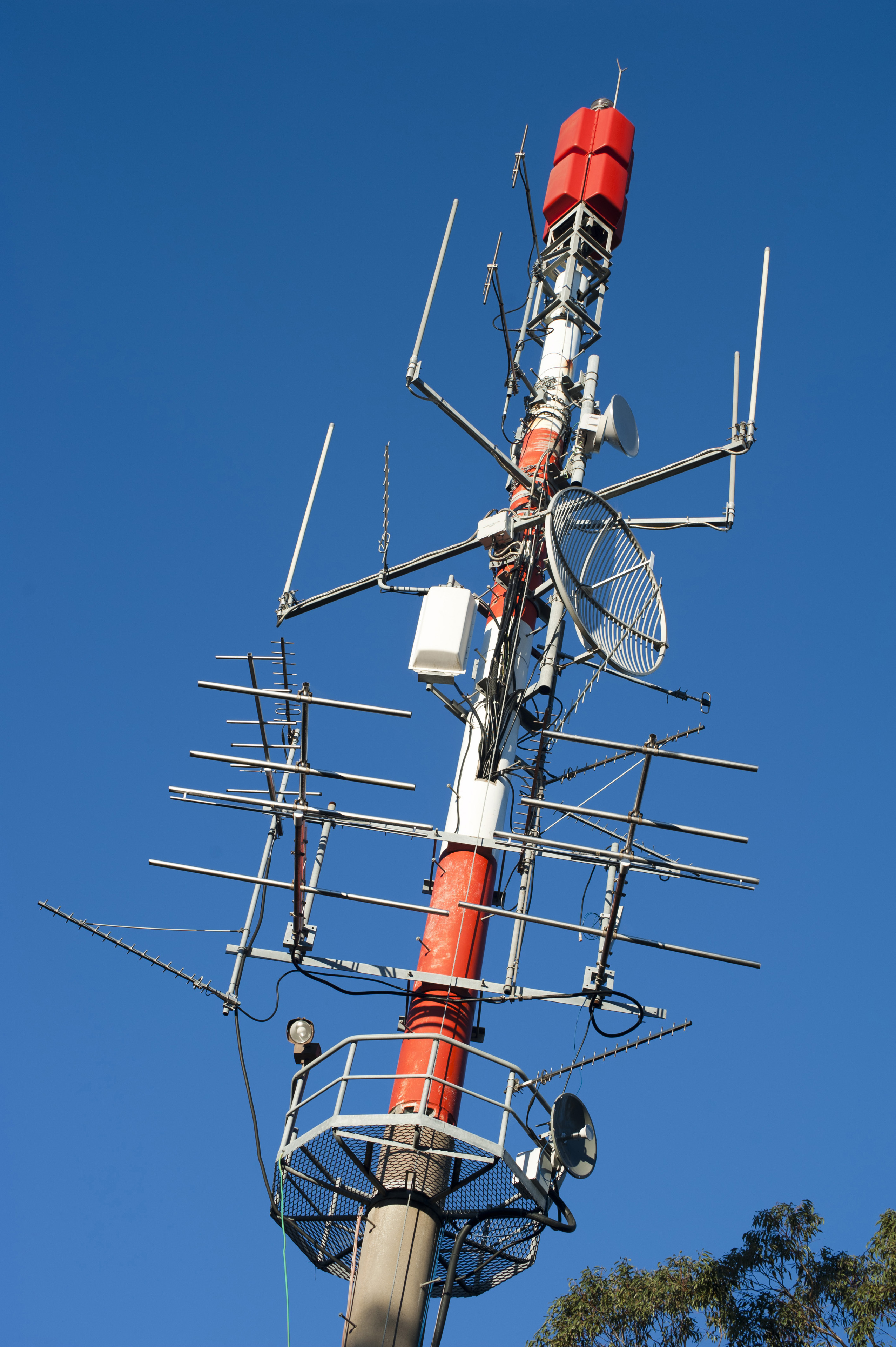 Active communication pole with transmitters, antennas and receivers for telecommunications, against a clear blue sky