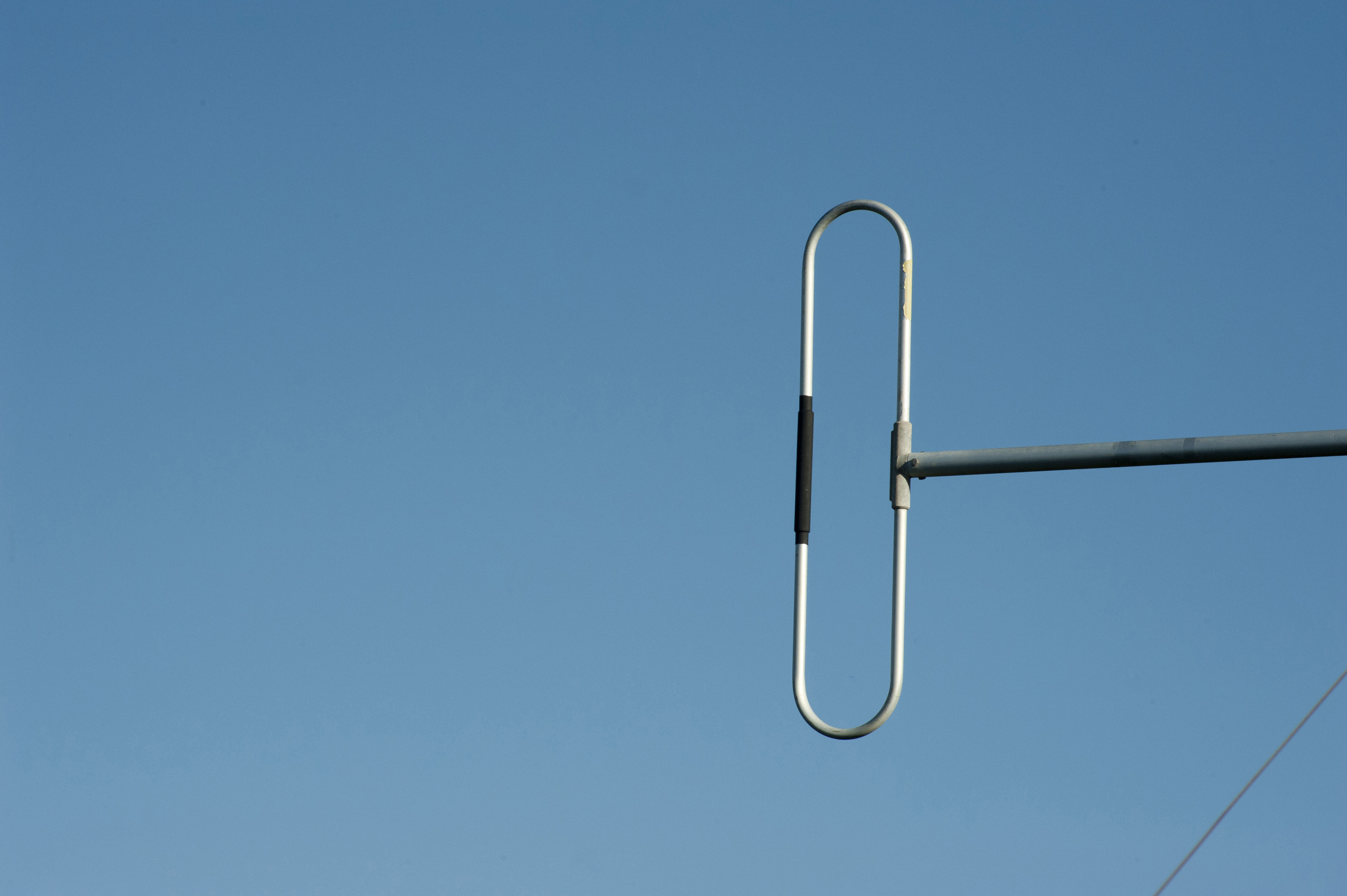 Dipole aerial metallic antenna used in radio and telecommunications, against a clear blue sky