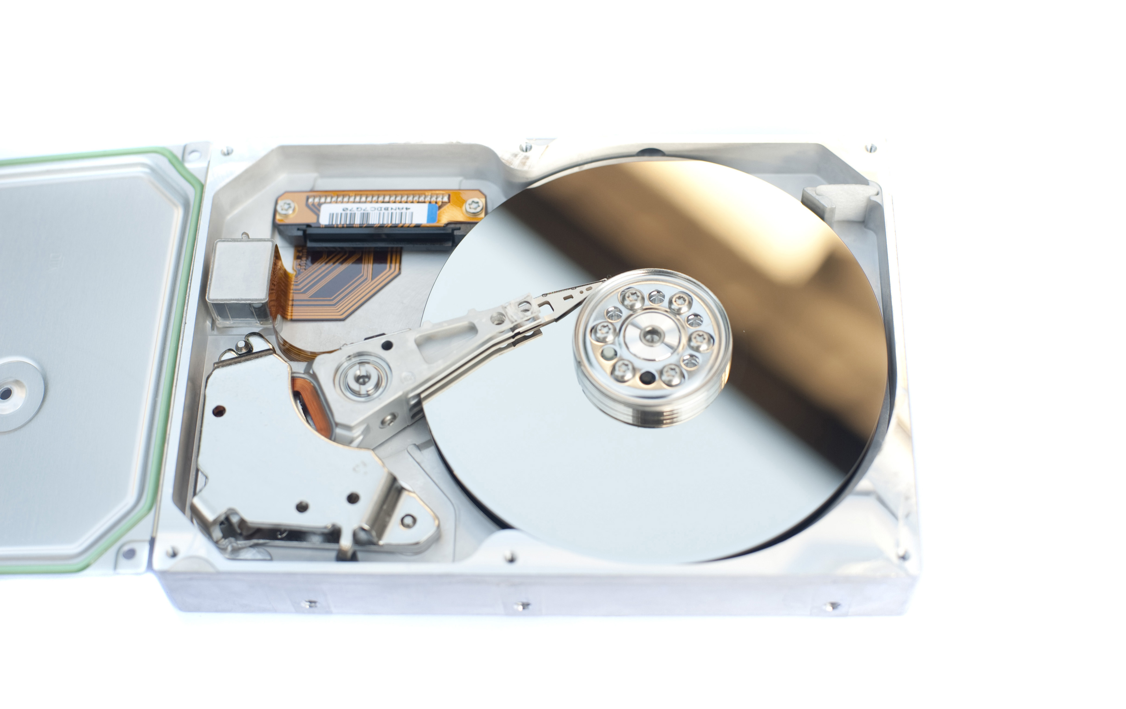 Detail of Open Hard Disk Drive Displaying Shiny Components, Open Case on White Background