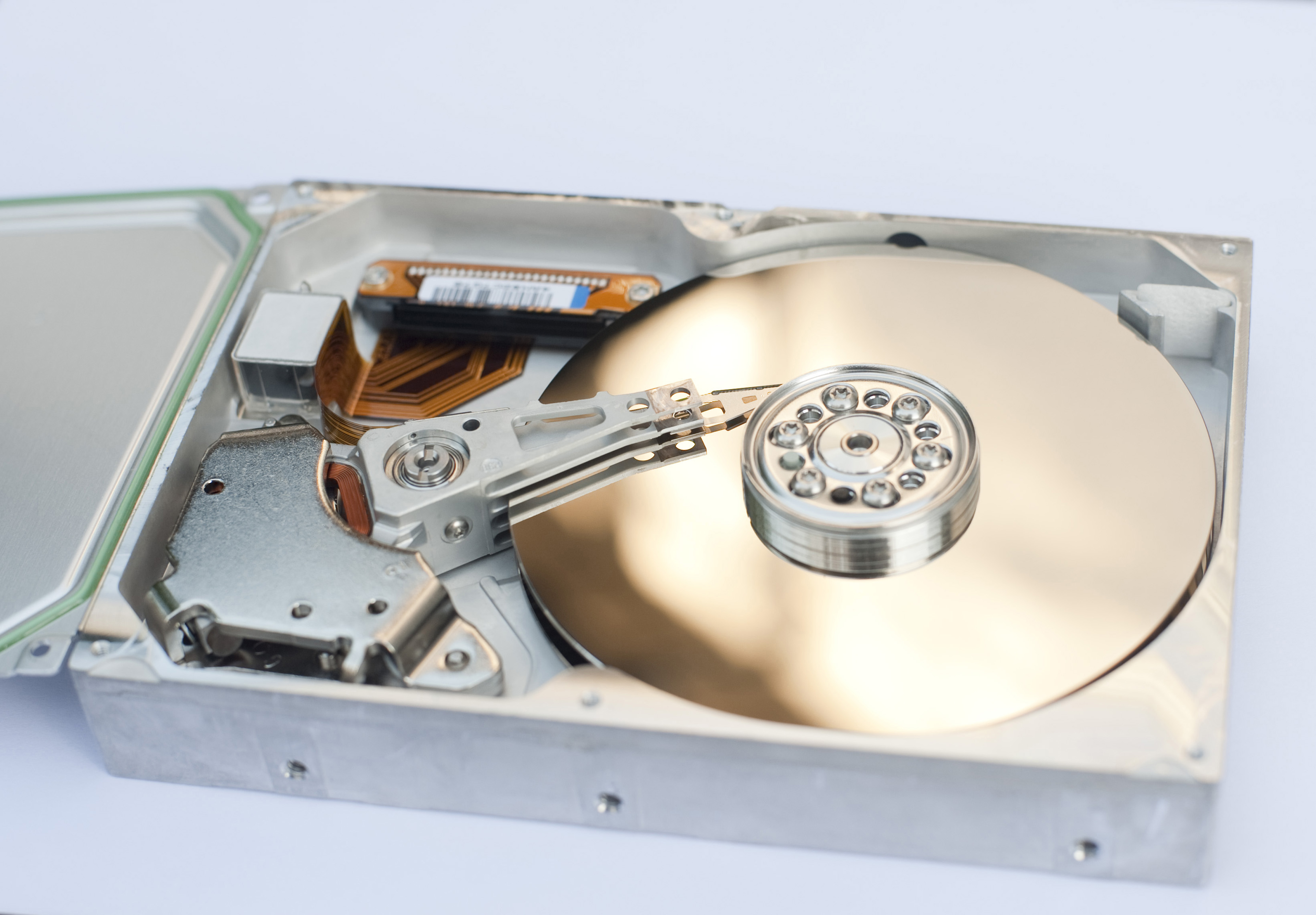 Close Up of Gold Colored Disk and Motor Hub of Hard Drive Computer Component on White Background