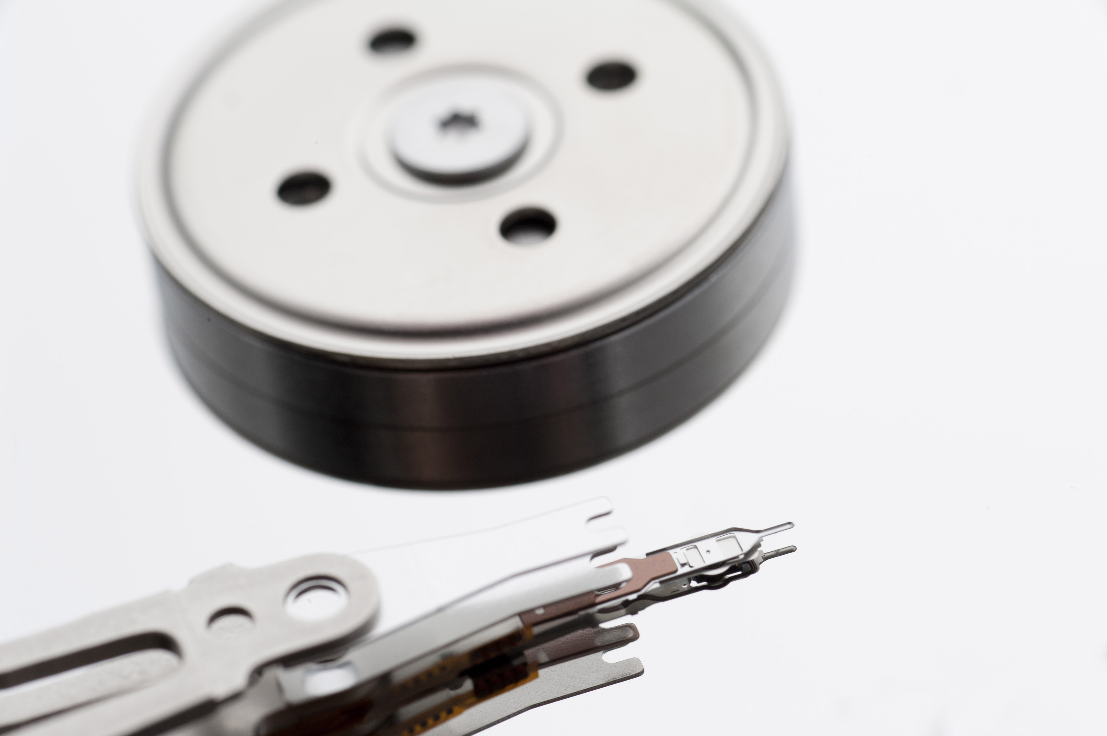 A close up of the internal components and parts of a computer hard disk isolated on a white background with copy space.