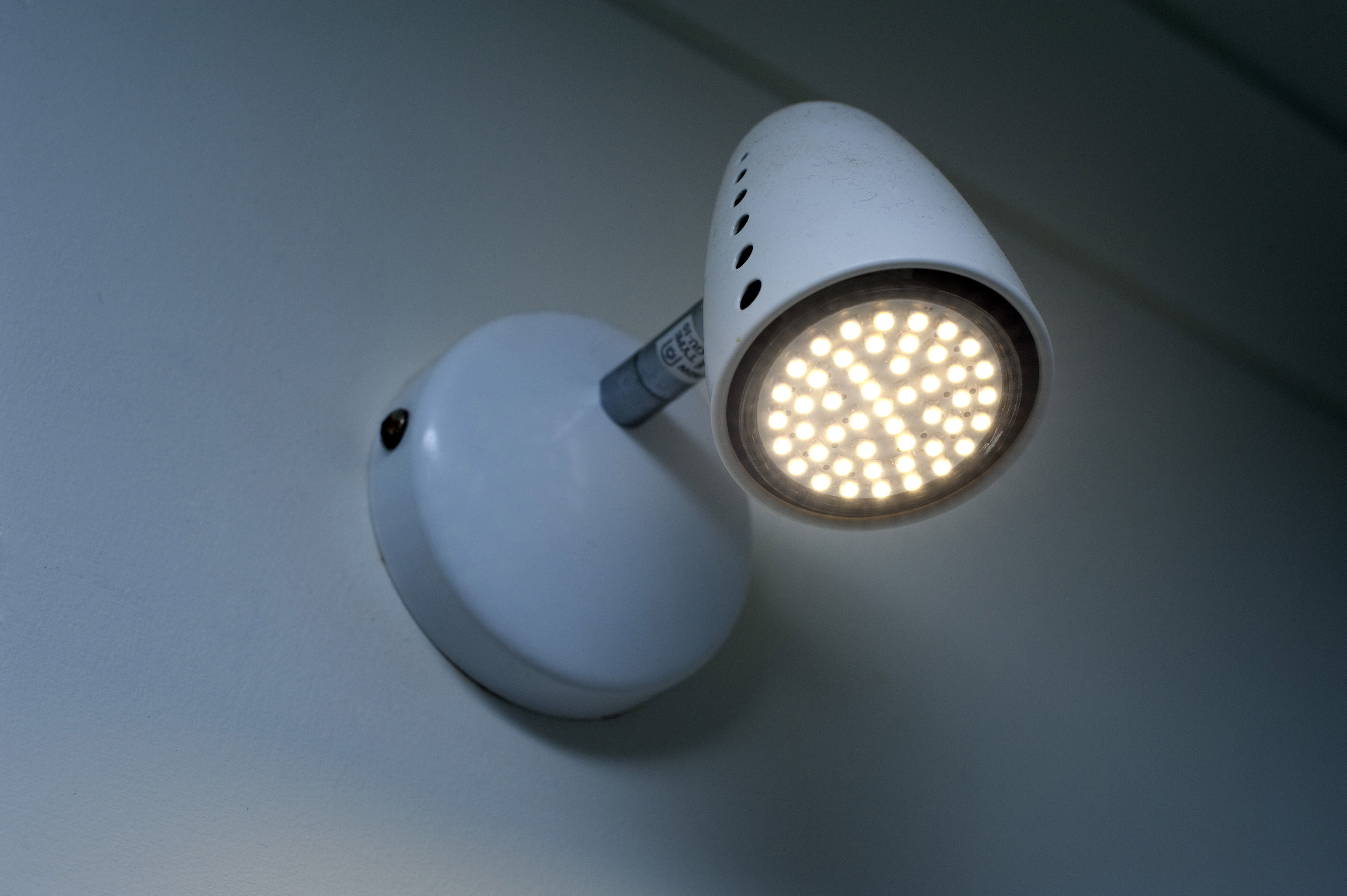 An downlight with illuminated LED's mounted on a white interior home wall.