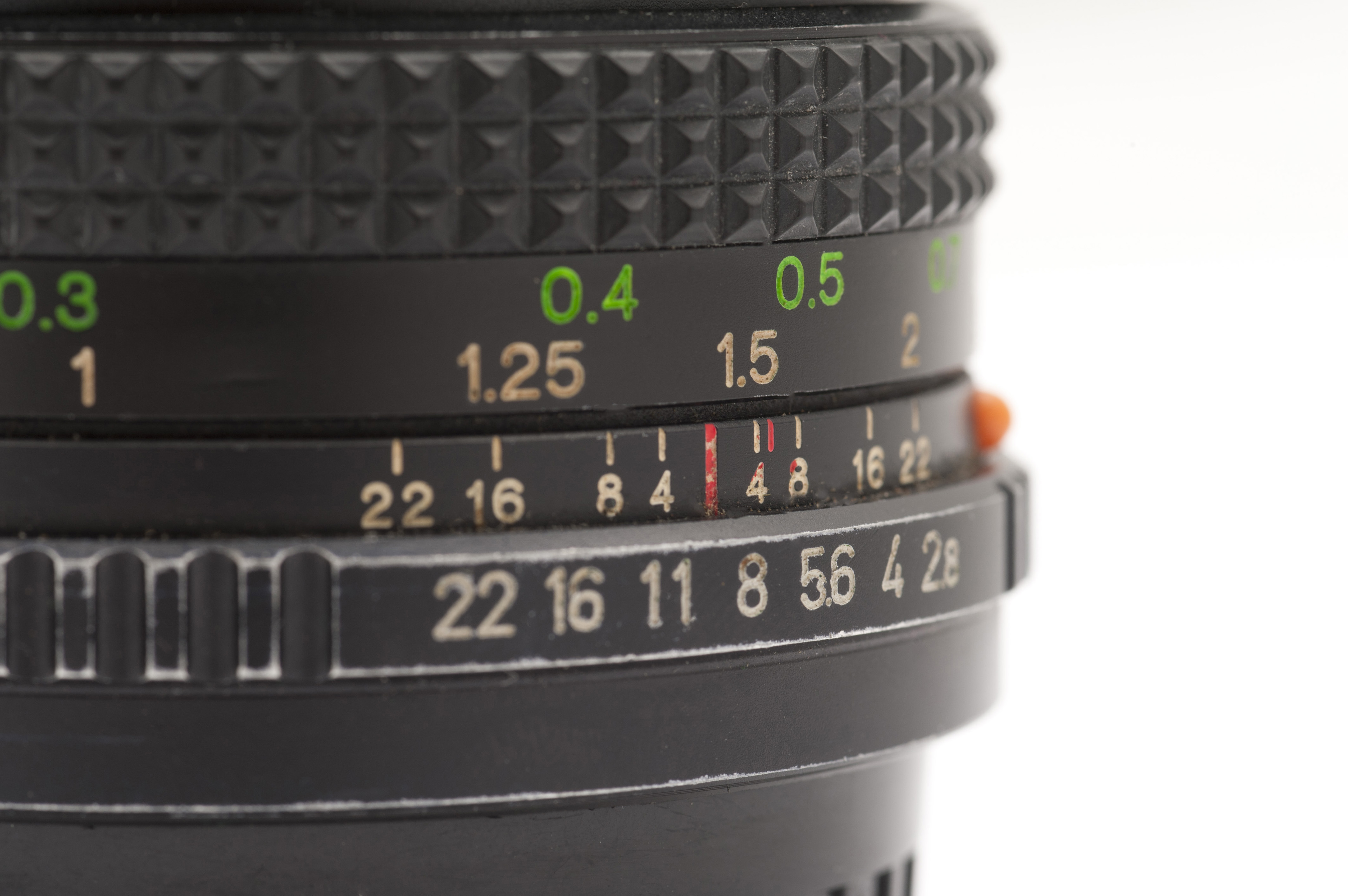 Close Up of Manual SLR Camera Lens Showing Aperture Readings and Focal Length with Copyspace on White Background