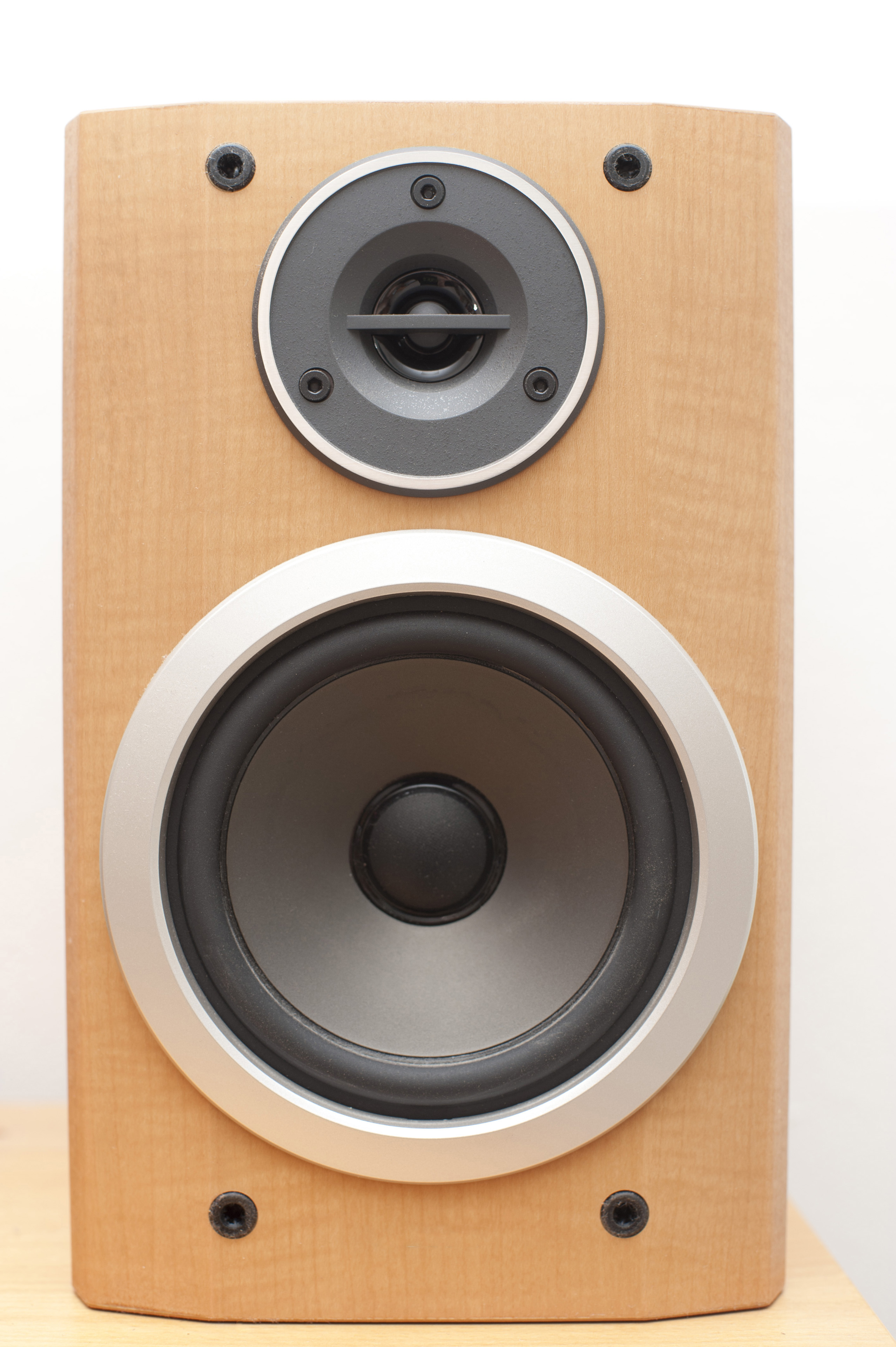 Plain brown speaker box with exposed speakers for sound and music broadcasting and entertainment over a white background