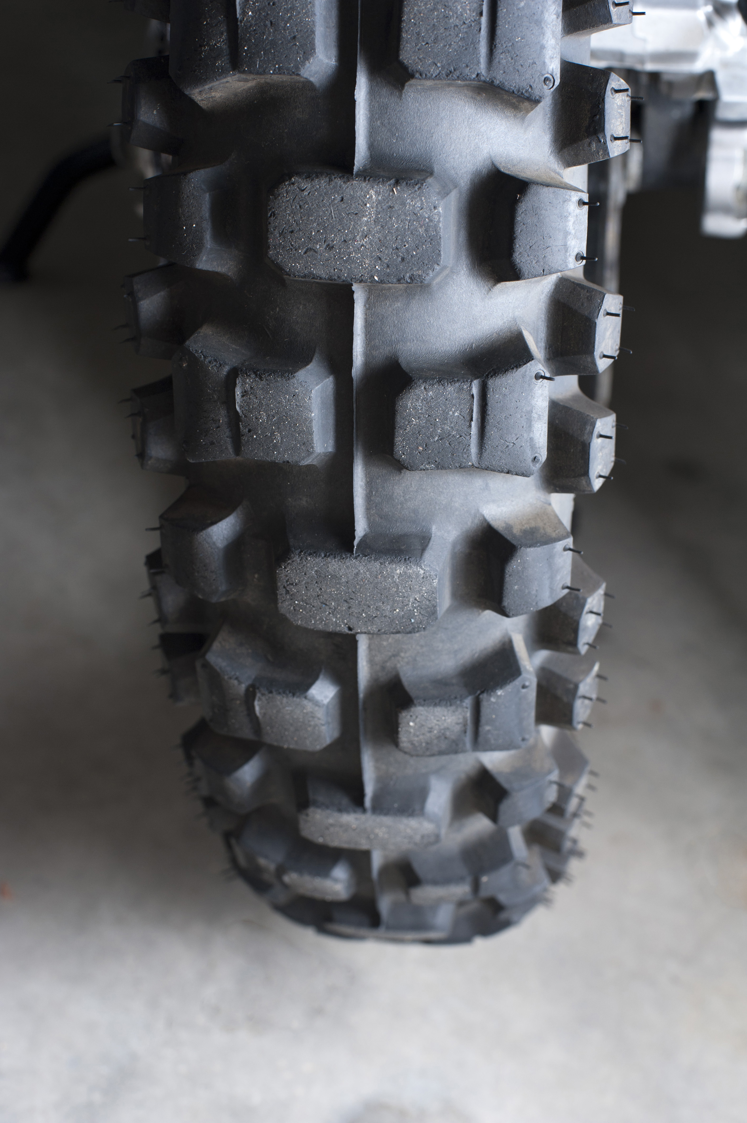 New tyre detail on a motorbike showing the rubber tread parked on a grey surface
