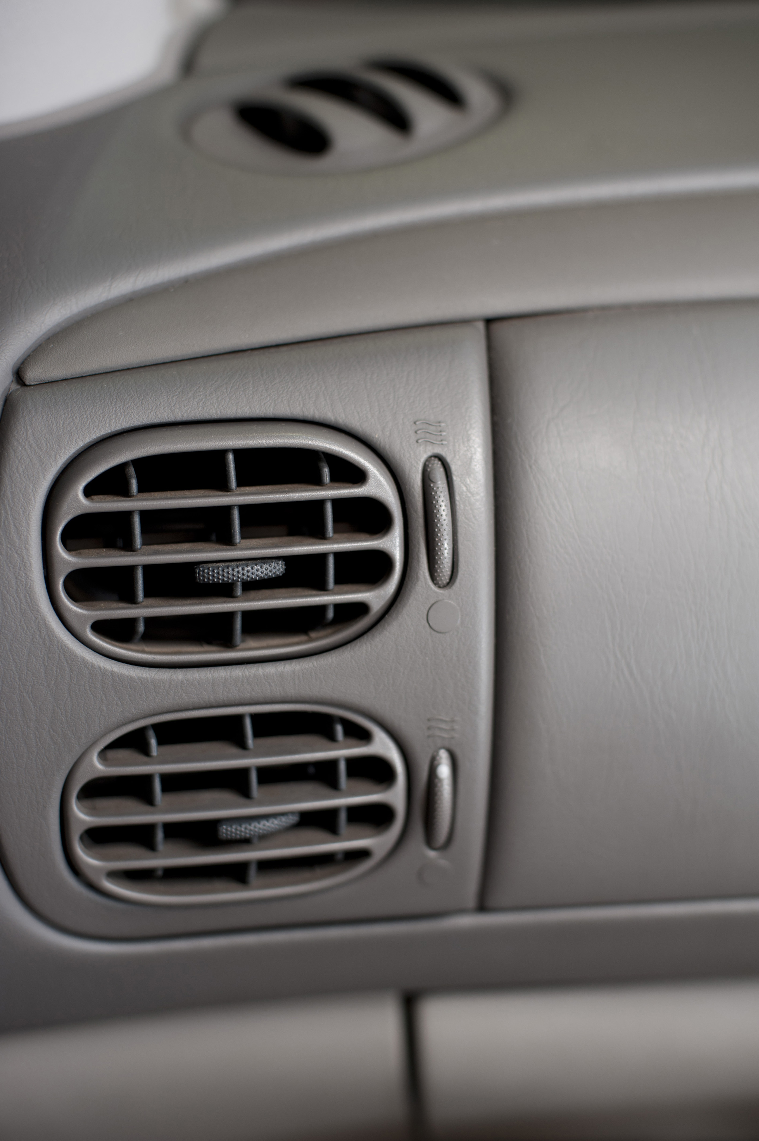Close up of two adjustable air vents on a car dashboard for air flow when using the air conditioner or heater, or for fresh air from the exterior