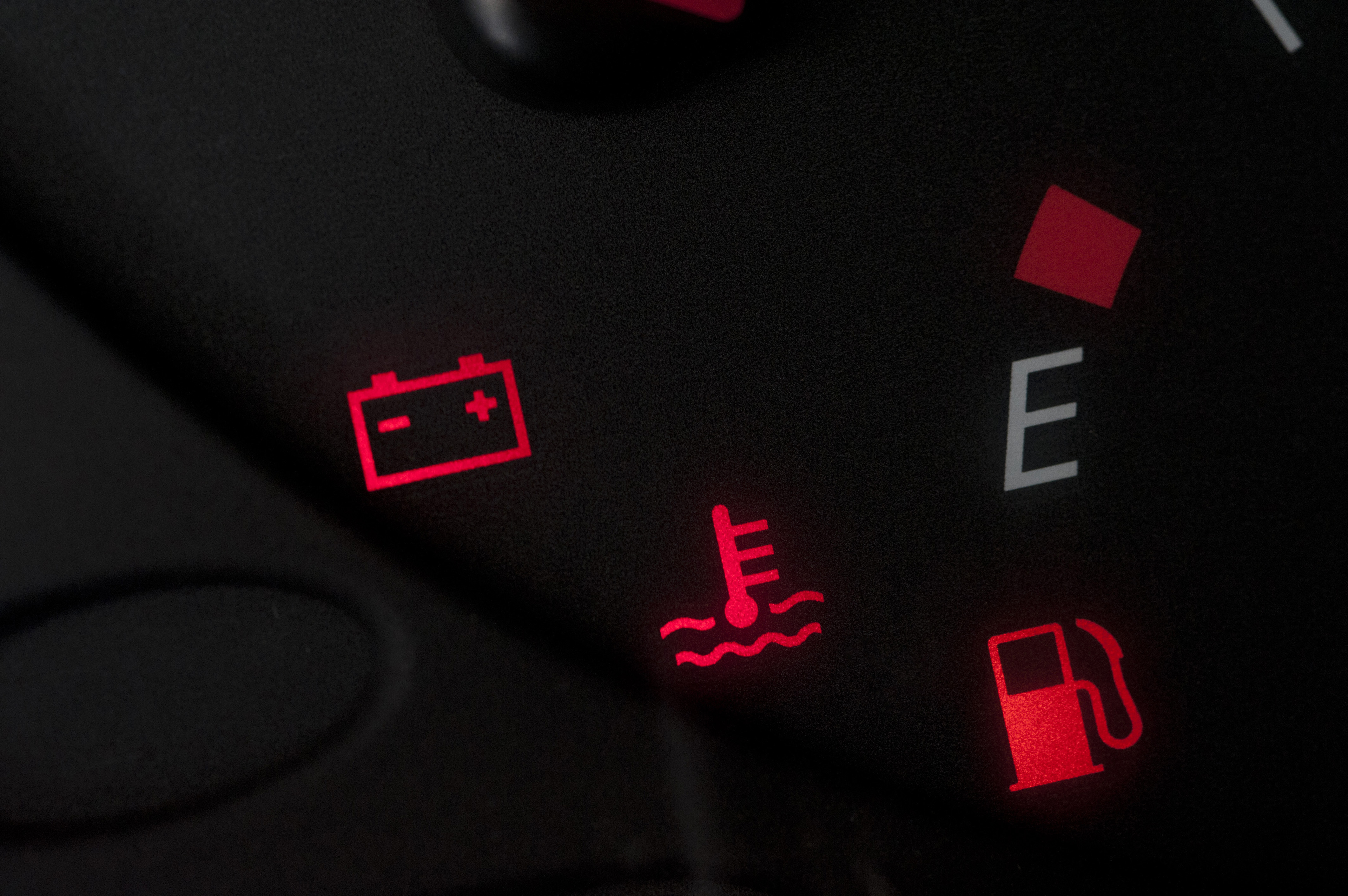 Illuminated red warning lights on a car dashboard during the ignition check showing the battery, temperature and fuel light