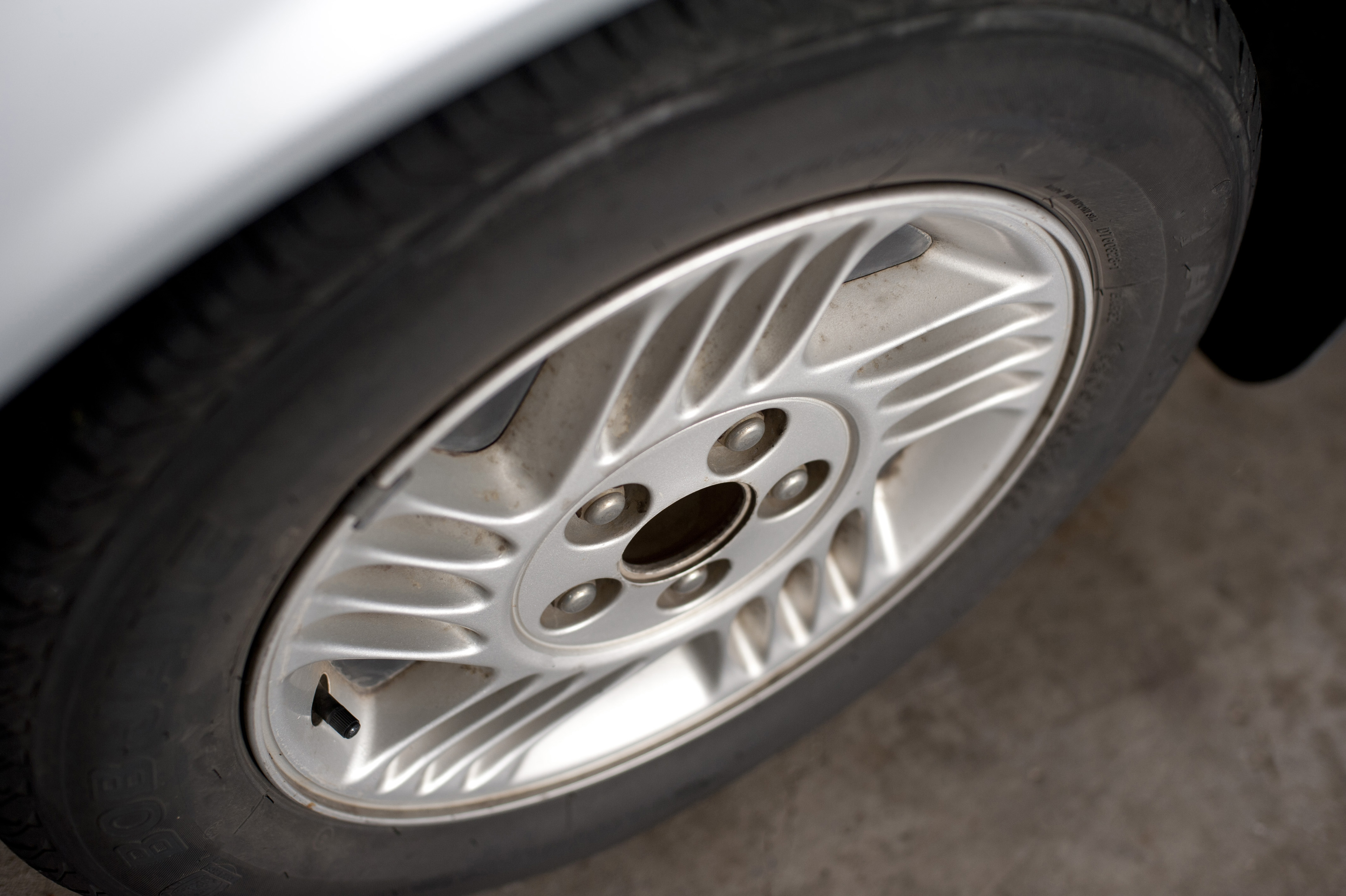 Wheel of a modern car tyre with a metallic ally sports rim viewed high angle parked on tarmac
